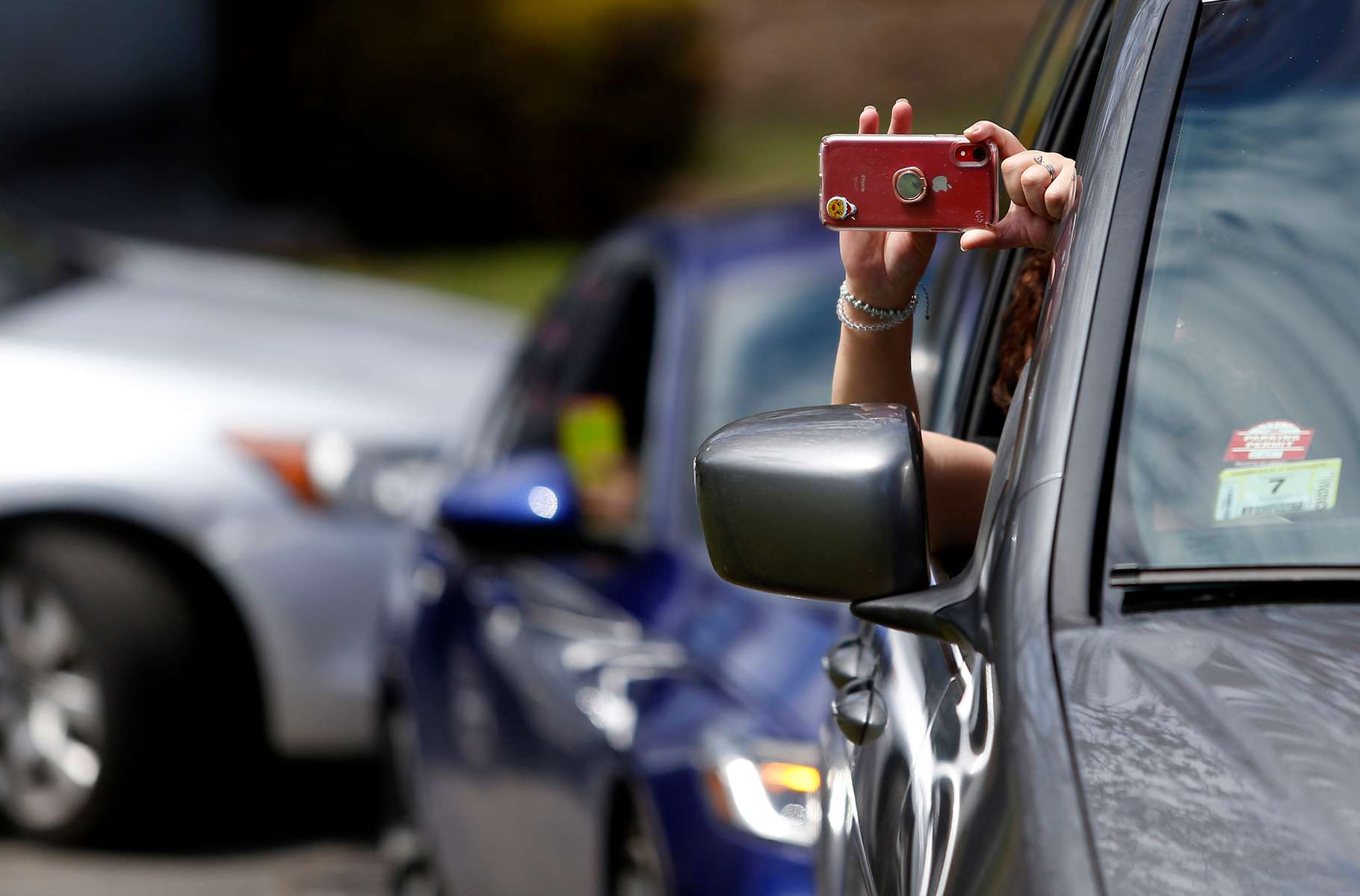 Everett, MA - 4/29/20 - A mourner holds a cell phone out to record as she attends Santos A. Rivas' funeral from inside her car. Due to strict social distancing guidelines only ten people are allowed outside of the car for graveside services at Woodlawn Cemetery in Everett. Friends and family lined three sides of the street surrounding the gravesite to pay their respects to Santos A. Rivas, who passed away from coronavirus or COVID-19. (Jessica Rinaldi/Globe Staff)