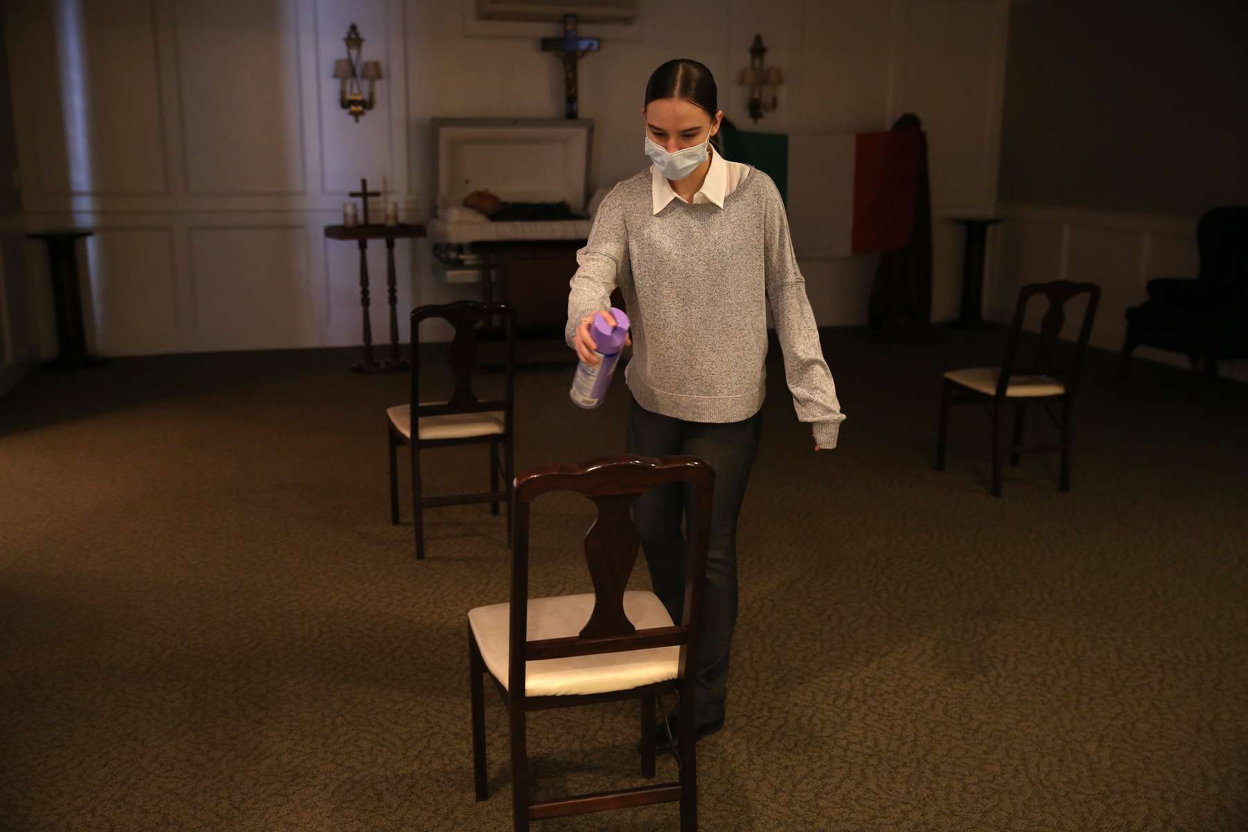 East Boston, MA - 4/29/20 - Apprentice funeral director Catie Ruggiero, sprays each chair down with lysol following a wake at Ruggiero Family Memorial Home in East Boston as funeral homes cope with a coronavirus or COVID-19 surge. (Jessica Rinaldi/Globe Staff)