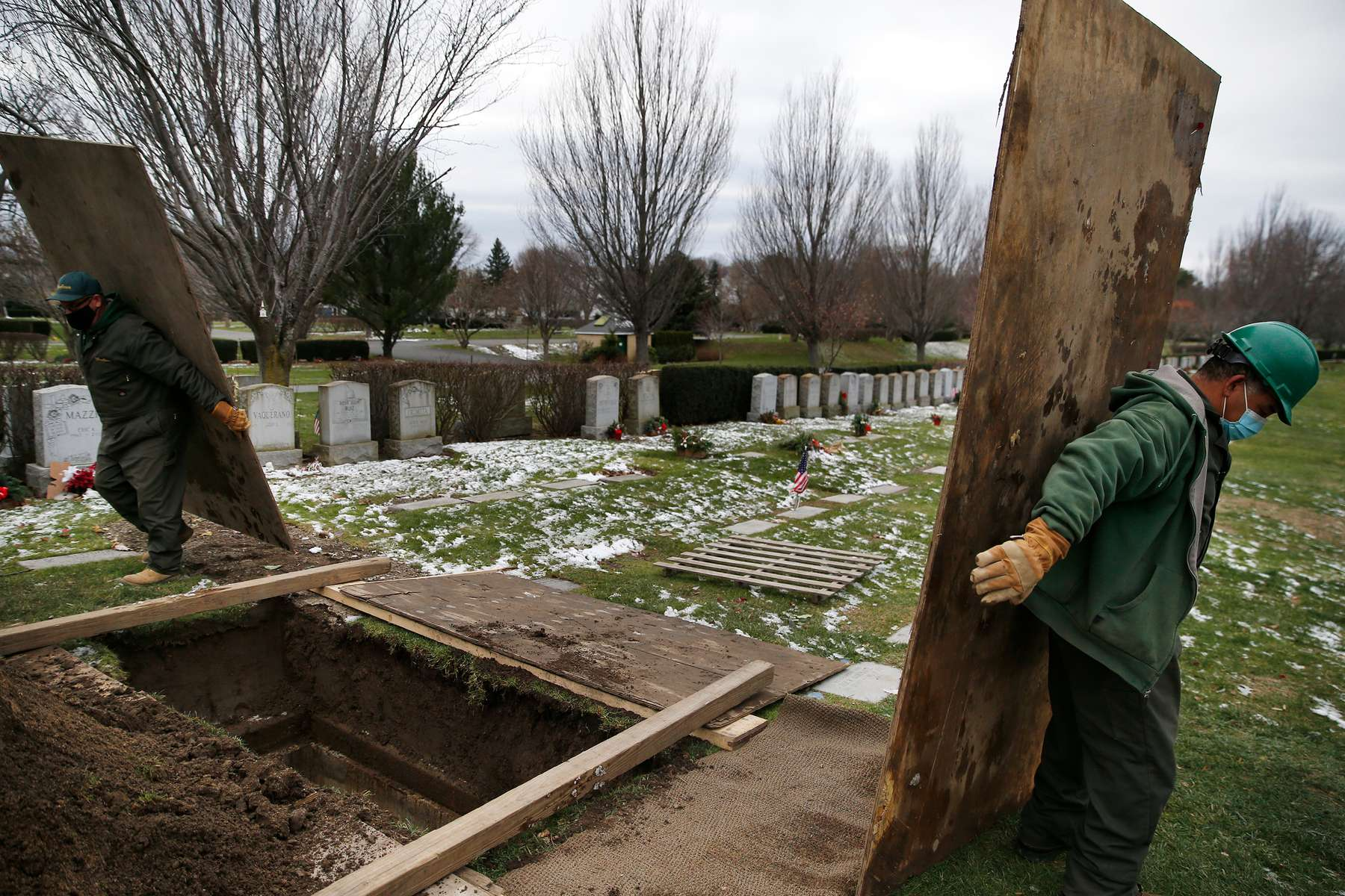 Everett, MA--12/8/20-- Roberto Arias (R) and Sean O'Donnell move pieces of wood in order to cover a grave that they've prepared for a burial that will take place the following day at Woodlawn Cemetery for a man who died of COVID-19.