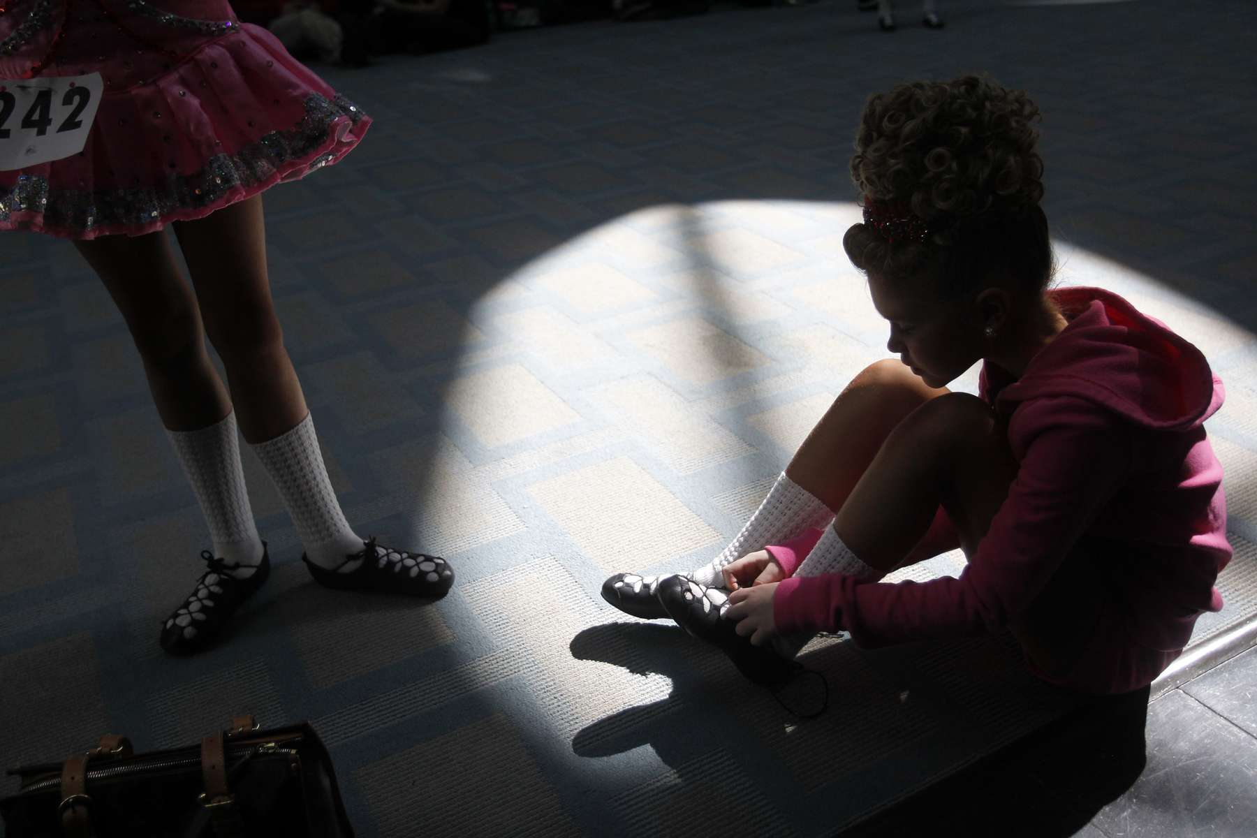 A competitor laces up her shoes in the hallway before competing in the World Irish Dancing Championships in Boston, Massachusetts March 24, 2013.