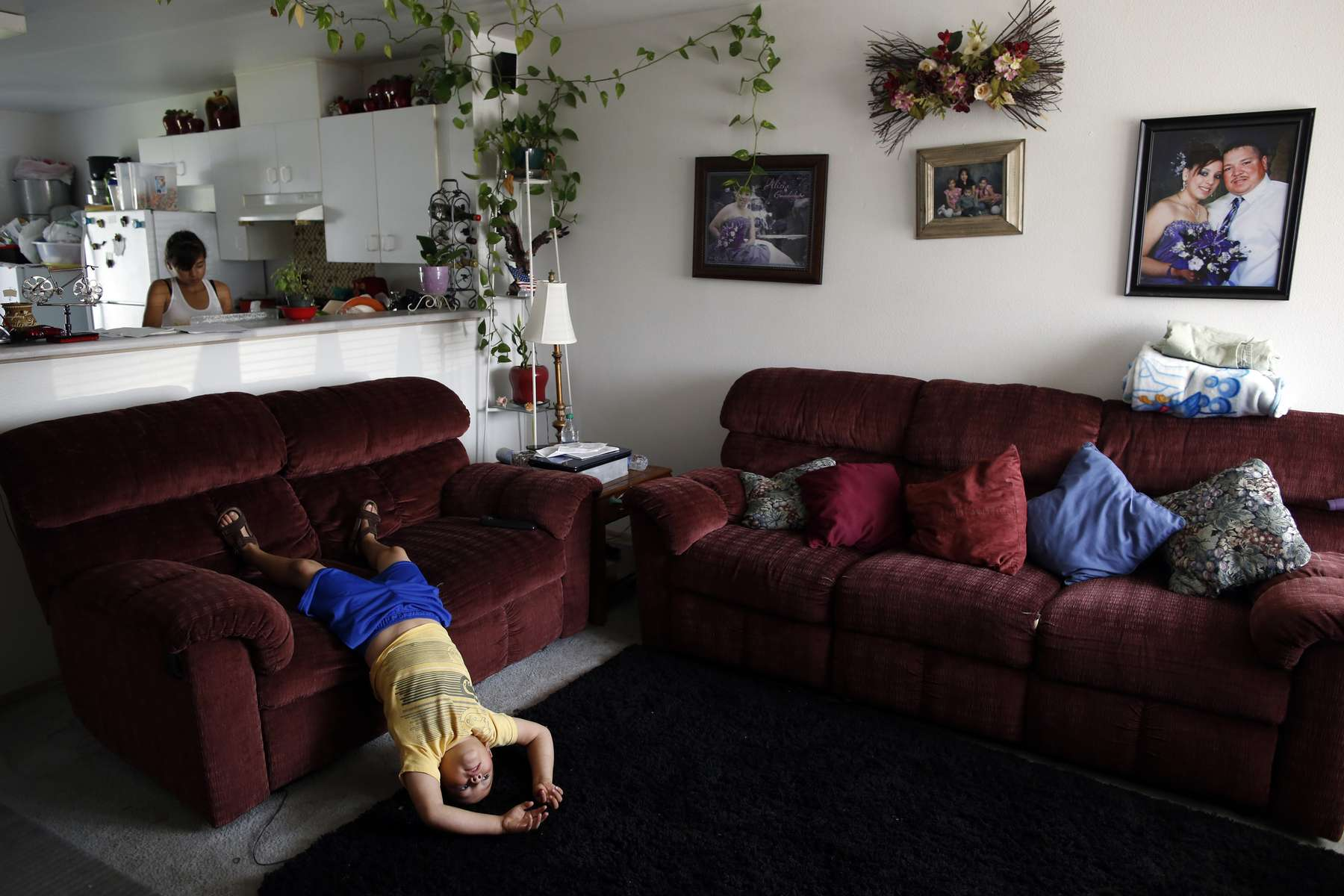 Eloy Cervantes, Jr., 6, plays while his older sister, Itai, 13, cleans the house and takes care of chores while their parents are at work in Mattawa, Wash., Aug. 23, 2013.Their parents Eloy and Flor Cervantes, have been in America for almost 20 years. Three of their four children were born in the United States and citizenship — or the lack of it — is constantly threatening to separate them. They say citizenship would be a solution for what has become a permanent way of life.