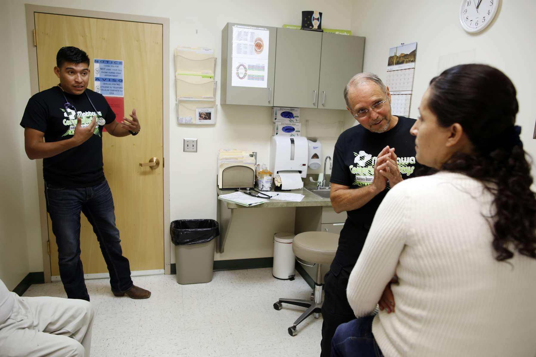 (L-R):  Medical Assistant Genaro Jimenez translates Dr. Daniel Sloane's question to Maria Granados inside the Mattawa Community Medical Clinic where Maria came after she fell from a ladder with a half full bag of apples after picking in the orchards in Mattawa, Washington, August 24, 2013.