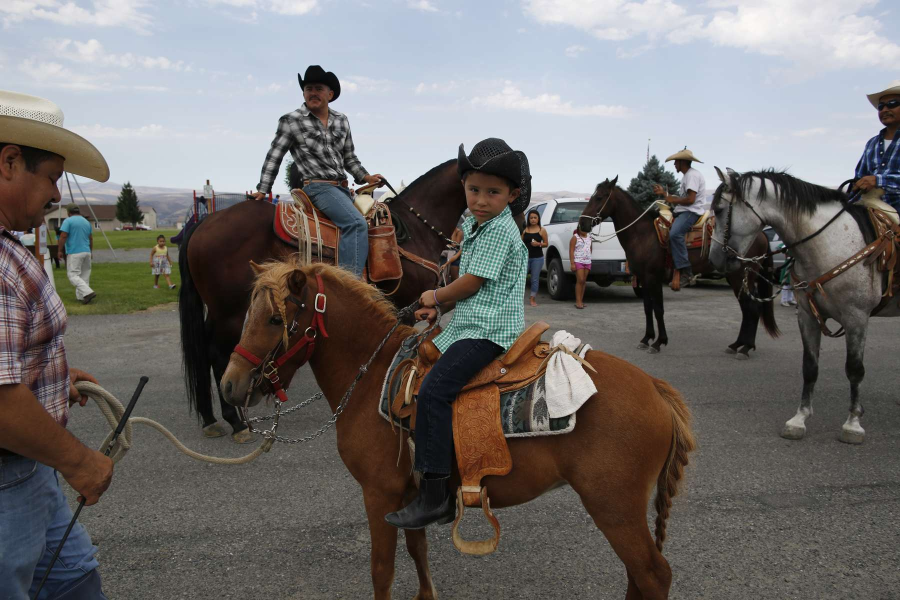 Juan Erazo, left, holds the lead line of his son, Azel's pony, Carinoso, as they ride during the Mattawa Community Day parade in Mattawa, Washington August 24, 2013. A few years ago, the city had canceled the longtime celebration because there were too few volunteers. But Maggie Celaya, a city councilor, and her sister, Lola Cruz, who teaches citizenship classes, worked to bring it back in 2012.