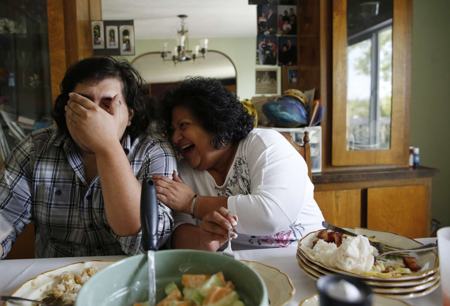 Cynthia de Victoria laughs with her son, Warren, 23, over breakfast at their home in Mattawa, Washington, August 25, 2013. de Victoria was the only Hispanic on the school board in 2009 when she was appointed to fill a vacancy. She urged Latino parents to attend meetings and prodded the white board members to learn how poverty affects learning. When she had to run for the seat in 2011, she lost to a white man.