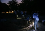 Falfurrias, Texas - Members of the Baylor forensics team and the University of Indianapolis Archeology and Forensics Laboratory shine flashlights so that their colleagues can start digging before the sun comes up as they work to exhume bodies of unidentified migrants who apparently died crossing the border and ended up buried anonymously in a pauper's grave in Falfurrias, Texas June 11, 2014.