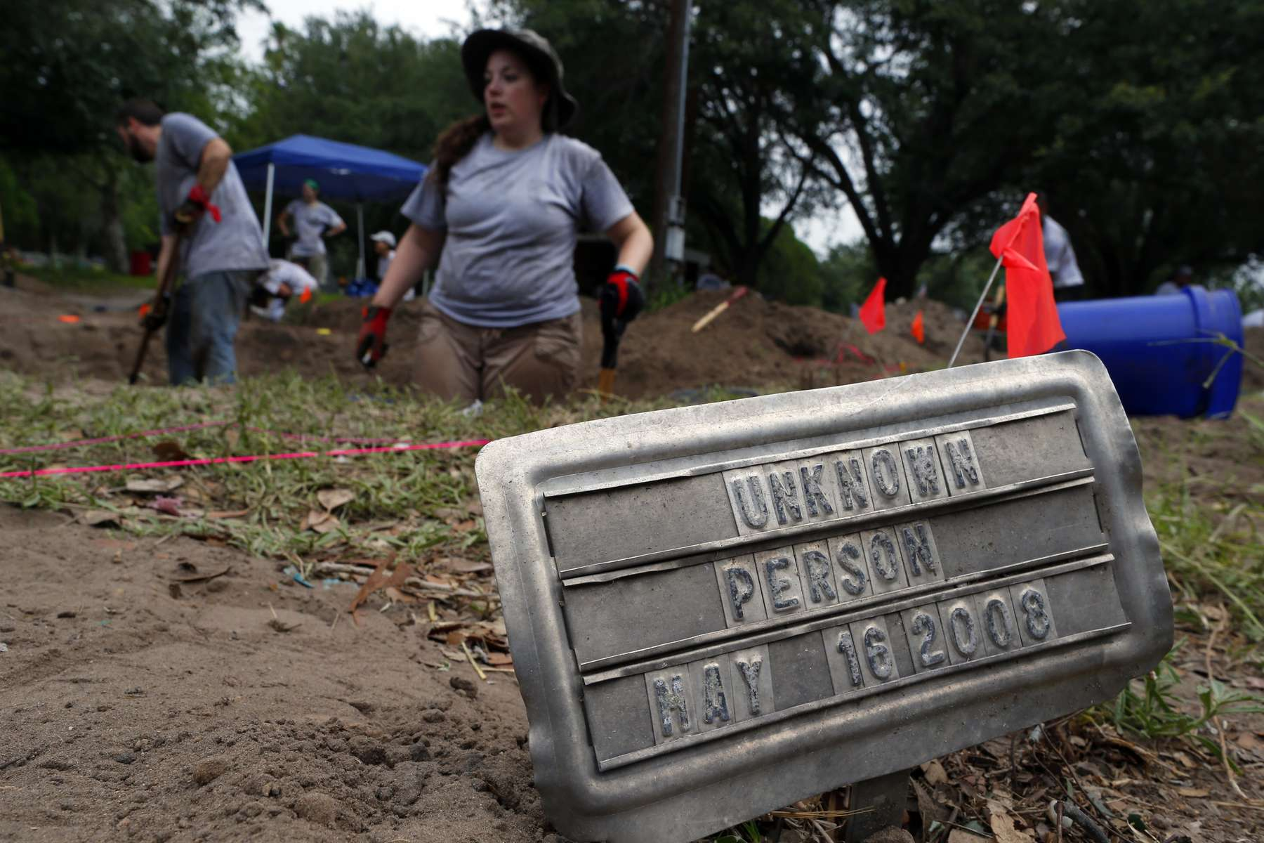 Falfurrias, Texas - University of Indianapolis Graduate Student Erica Christensen, 24, (C) works to exhume a body of an unidentified migrant who apparently died crossing the border and ended up buried anonymously in a pauper's grave in Falfurrias, Texas June 10, 2014.