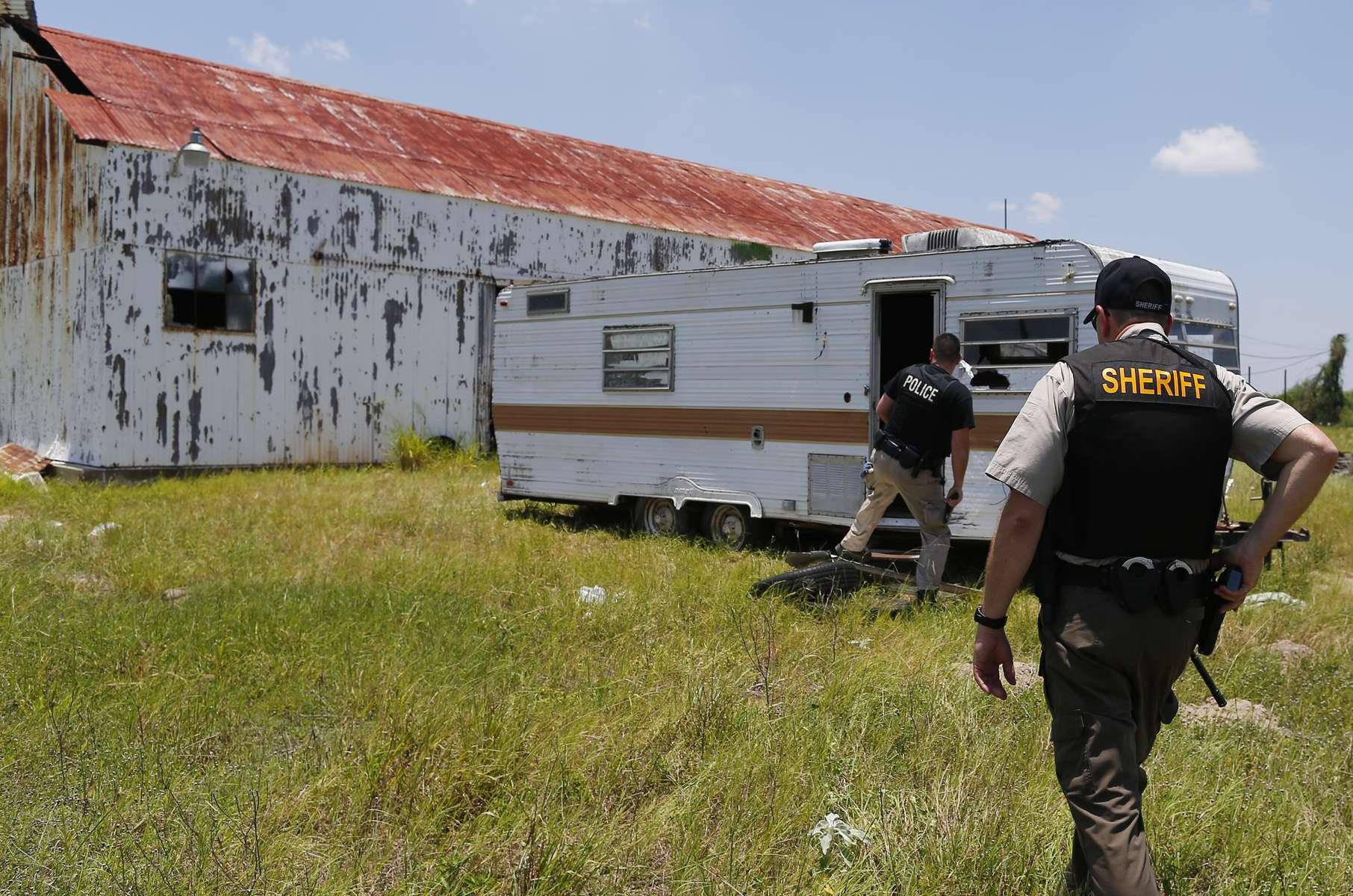 Falfurrias, Texas -  Cameron Coleman of the Hidalgo County Sheriff's Department (L) and Daniel Walden Chief of Dona ISD Police Department walk towards a trailer where migrants are known to wait and watch the street as they make their trek through a ranch in Falfurrias, Texas June 11, 2014. Both officers are part of Brooks County Sheriff's Office Rescue Posse an effort by local police to help lend an additional hand to Falfurrias who is understaffed and underfunded.