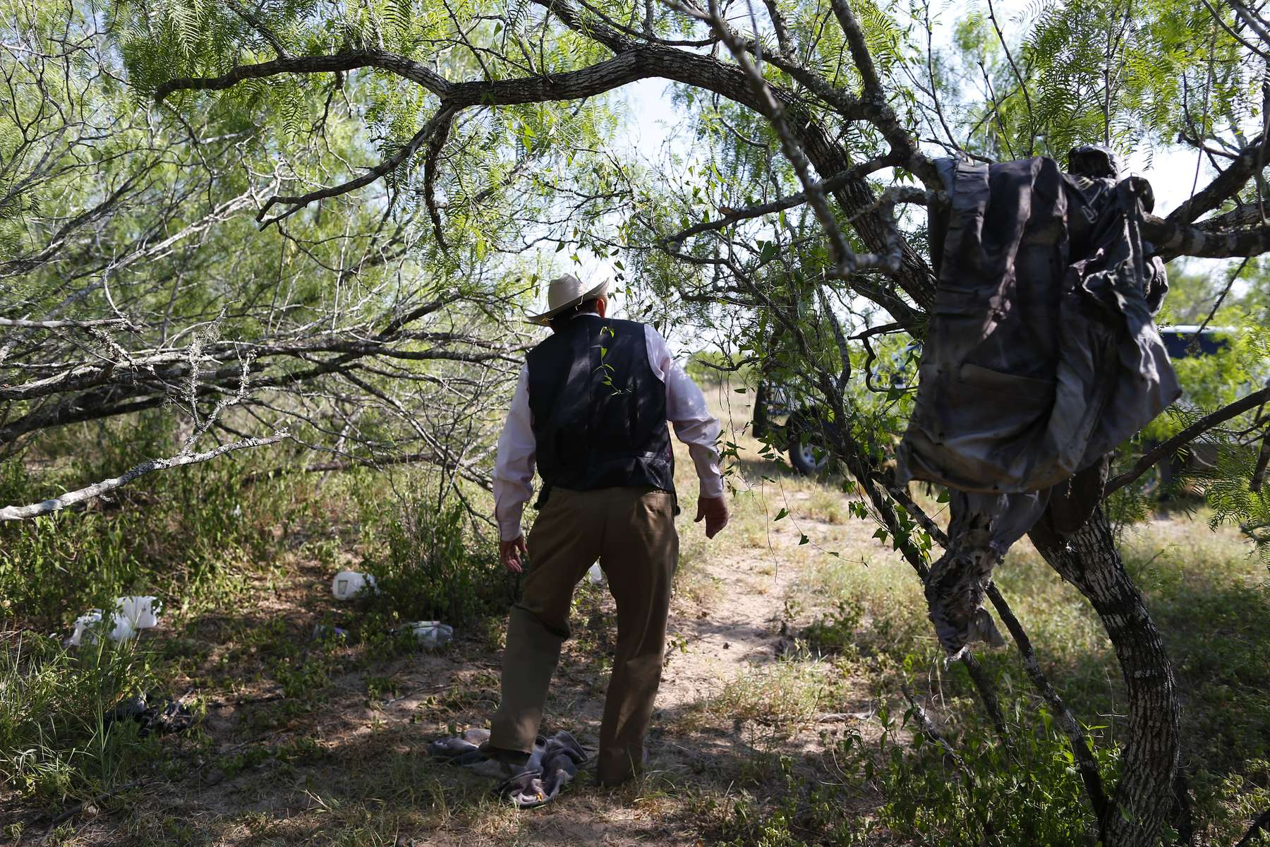 Falfurrias, Texas -  Lavoyger Durham walks through land on the ranch he works where clothing is left behind by migrants in Falfurrias, Texas June 12, 2014.