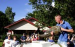 A noodler pulls his catfish out of the tank in front of a small crowd gathered at a Noodling Tournament in Pauls Valley, Oklahoma June 30, 2007.