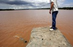 A man watches as a noodler searches for catfish in Pauls Valley, Oklahoma June 30, 2007.