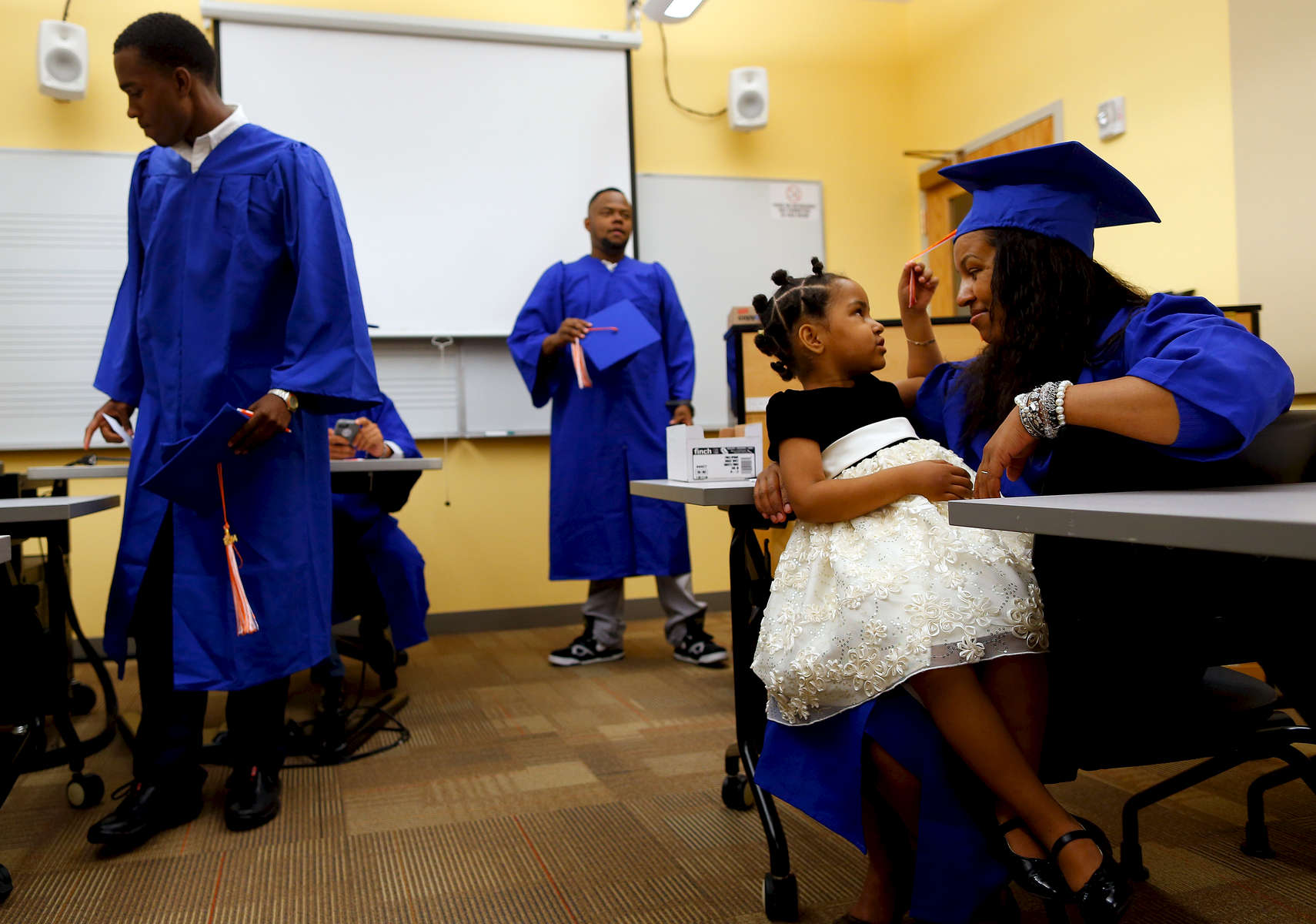 Boston, Massachusetts -- 08/27/2014-- Sanjoana Fernandes, 34, (R) who is headed to Bunker Hill Community College leans in as her daughter Synali, 3, grabs the tassel on her graduation cap before College Bound Dorchester Matriculation Ceremony in Boston, Massachusetts August 27, 2014.
