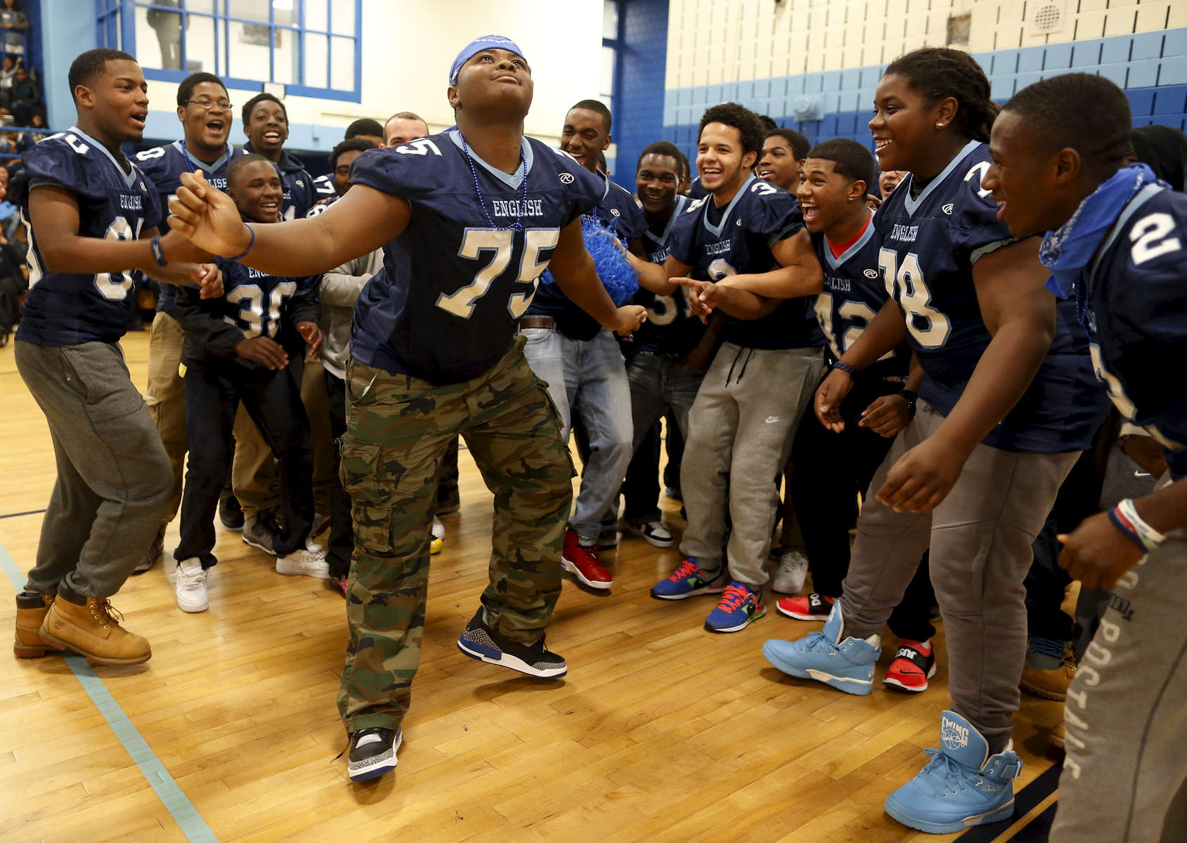 Jamaica Plain, Massachusetts -- 11/26/2014-- English High Marching Band member and football player Keishawn Guillaume, 16, of Jamaica Plain (C) dances with members of the football team during a pep rally at English High School in Jamaica Plain, Massachusetts November 26, 2014.