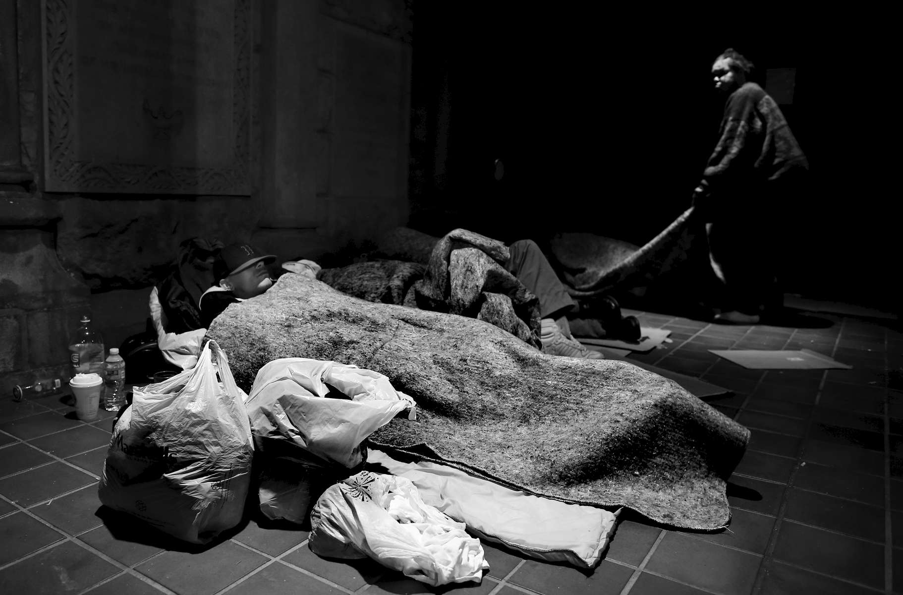 Boston, Massachusetts -- 11/05/2014-- With a lack of spaces available in women\'s shelters former Long Island resident Kayla Nauti, 34, (L) found a space to sleep outside at Trinity Church as Susan Bakerjones, 48, laid out a blanket beside her.