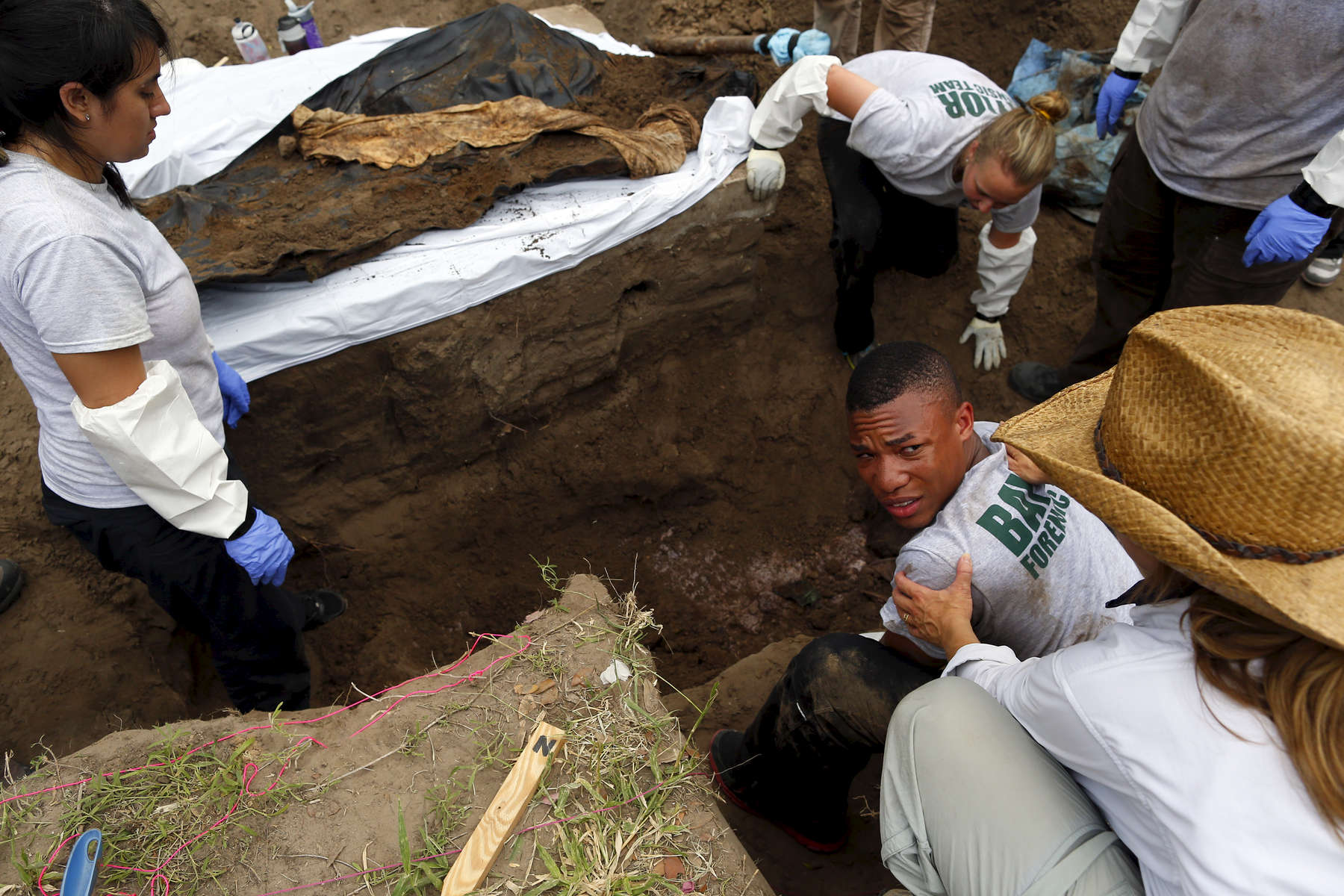 Xavier Colbert, 22, a Senior at Baylor (C) reacts as he sees another body underneath the one they just pulled out of a grave in Falfurrias, Texas June 10, 2014.