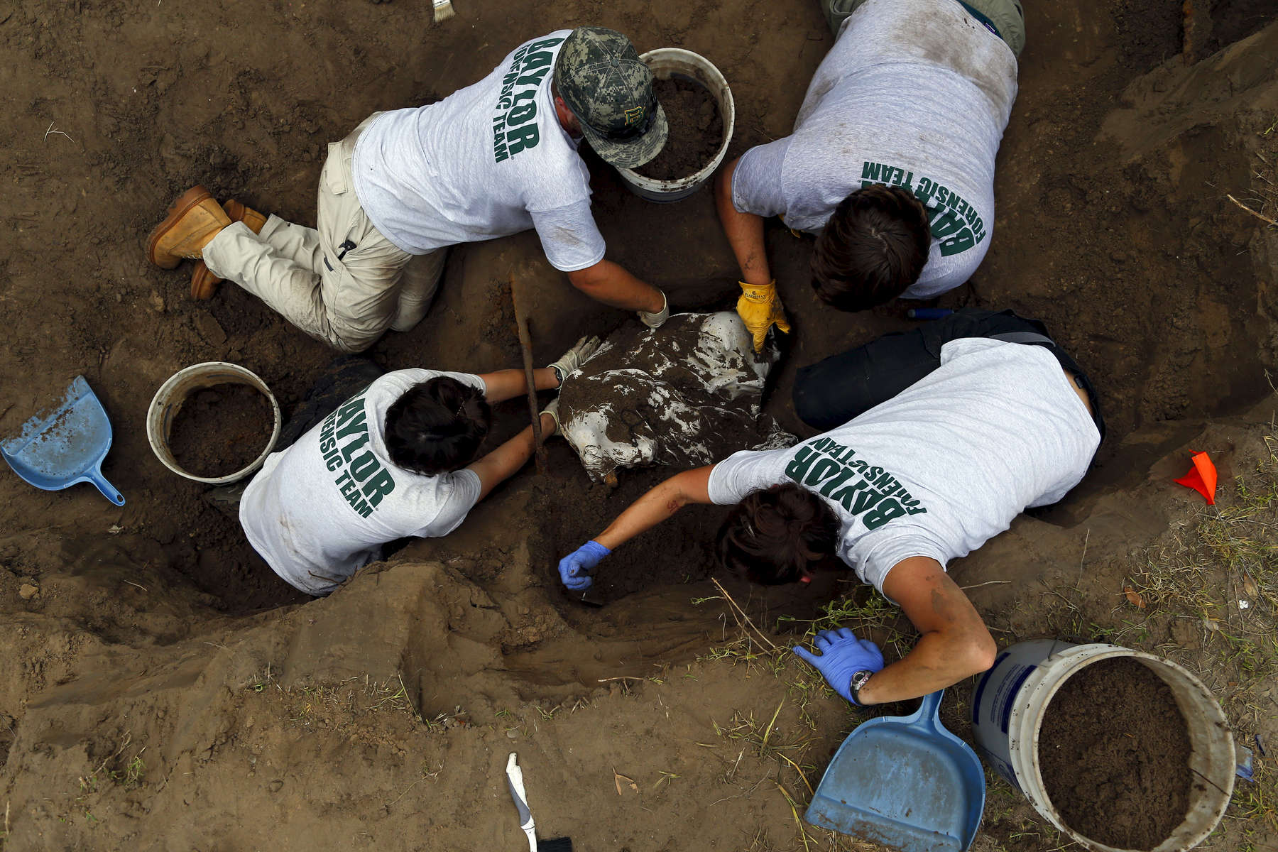 In 2012, 129 bodies were found in Brooks County, more than half were unidentified. The following year officials discovered 87 bodies, and 44 percent were unidentified. Here members of the Baylor forensics team carefully remove the dirt surrounding a body as they work to exhume it in Falfurrias, Texas June 10, 2014.