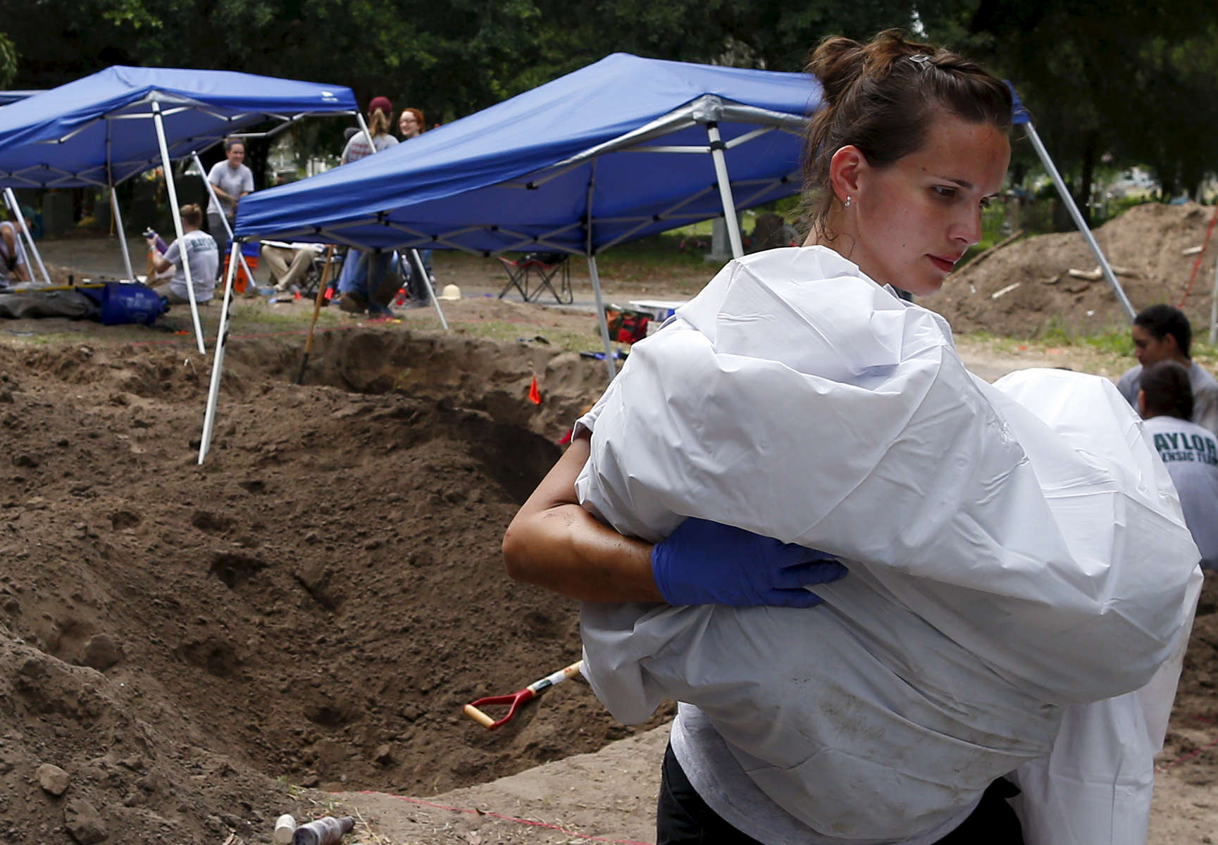 In Sacred Heart Cemetery, students found corpses stuffed into body bags, rolled in blankets, and placed in garbage bags. Ashley Roy, 30, who works as a crime scene tech for the Waco Police Department in Waco, Texas carried a body of an unidentified migrant after helping members of the Baylor forensics team to exhume it in Falfurrias, Texas June 10, 2014.