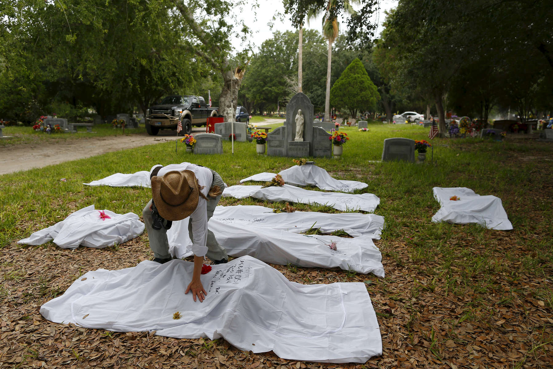 Lori E. Baker, Ph.D. places her hand on one of the eight body bags that members of the Baylor forensics team exhumed from a pauper\'s grave in Falfurrias, Texas June 10, 2014.