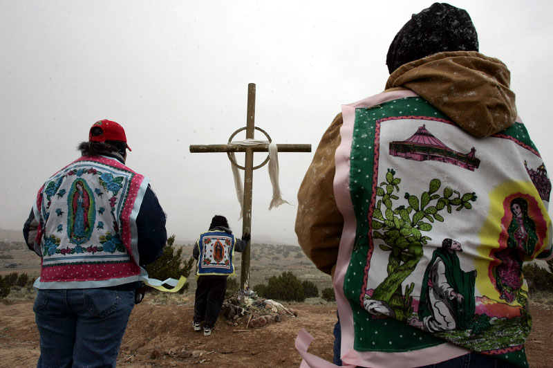 Women stop to pray at a cross during a pilgrimage to El Santuario de Chimayo in Chimayo, New Mexico April 7, 2007.