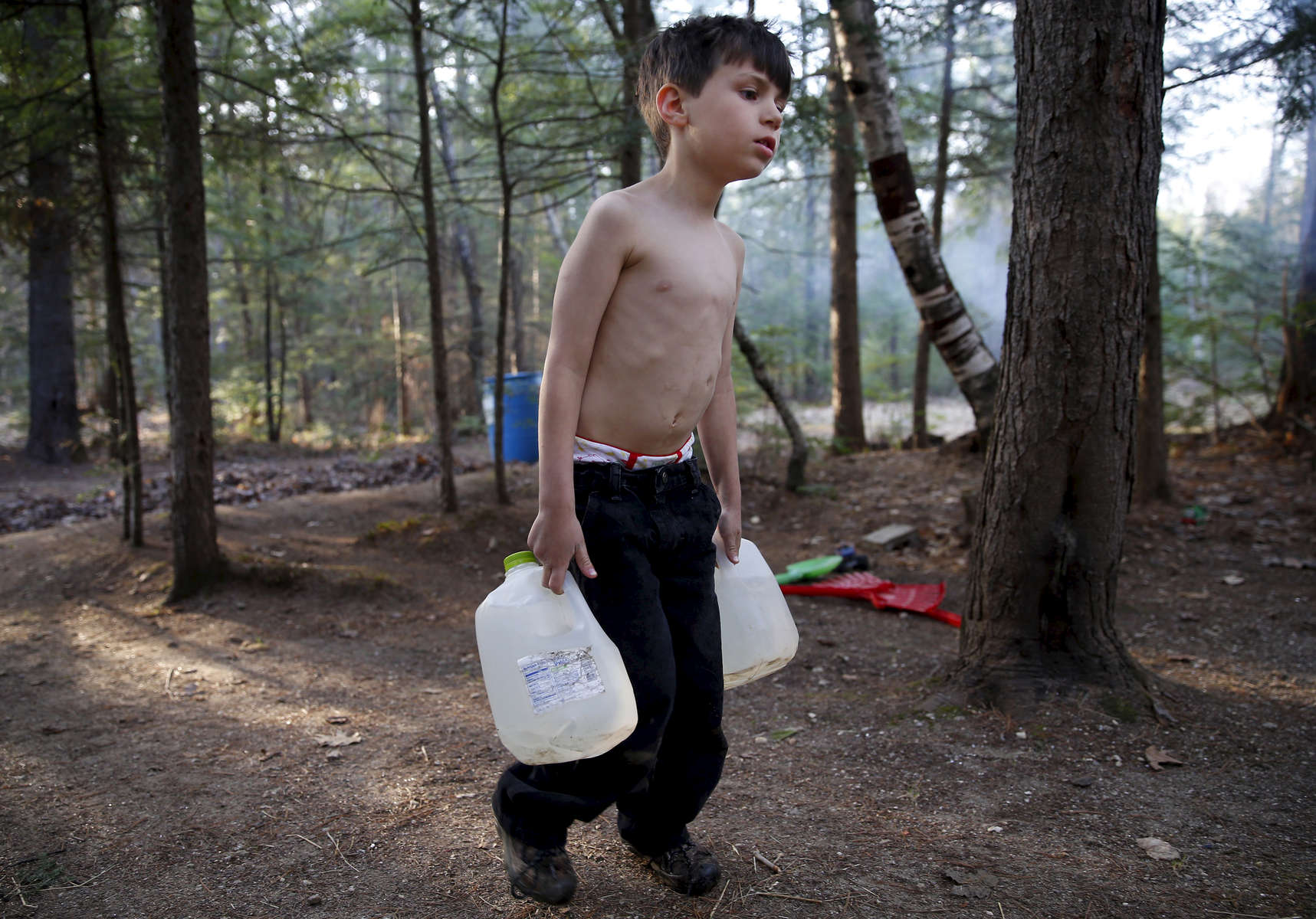 Oxford, Maine -- 5/4/2015--  Strider carried gallon jugs of water over to Lanette after filling them from a spigot behind the camper so that she could wash dishes and heat some of it on the small stove inside to bathe the boys with a washcloth. Jessica Rinaldi/Globe Staff