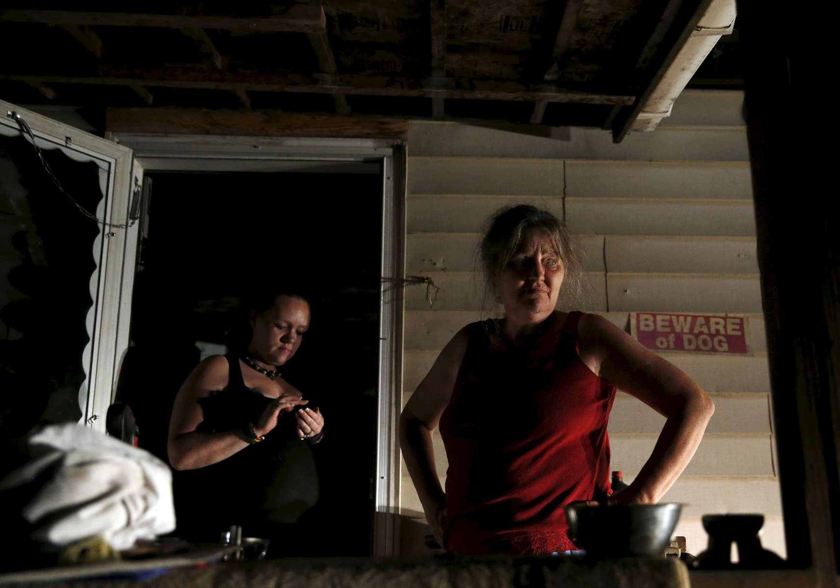 Oxford, Maine -- 5/28/2015-- As the night went on it became clear that they were not going to be able to take all of their possessions with them. Michael's fiancee, Ashly, (L) stood in the doorway with Lanette as they took a break from packing up the family's belongings on the night of the eviction. Jessica Rinaldi/Globe Staff