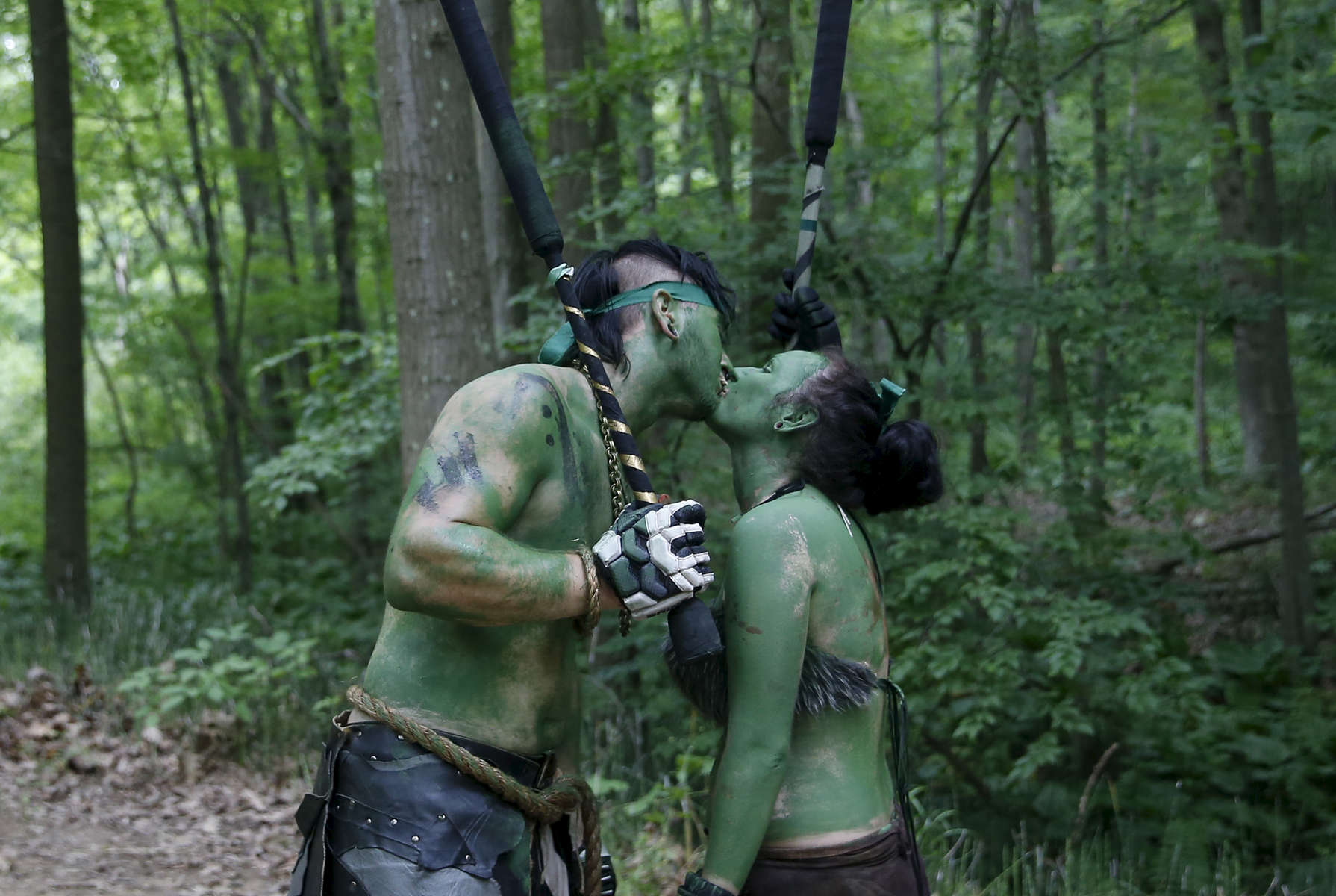 Slippery Rock, PA -- 6/22/2017 -  A couple paused for a kiss as they passed each other during a battle in the woods.