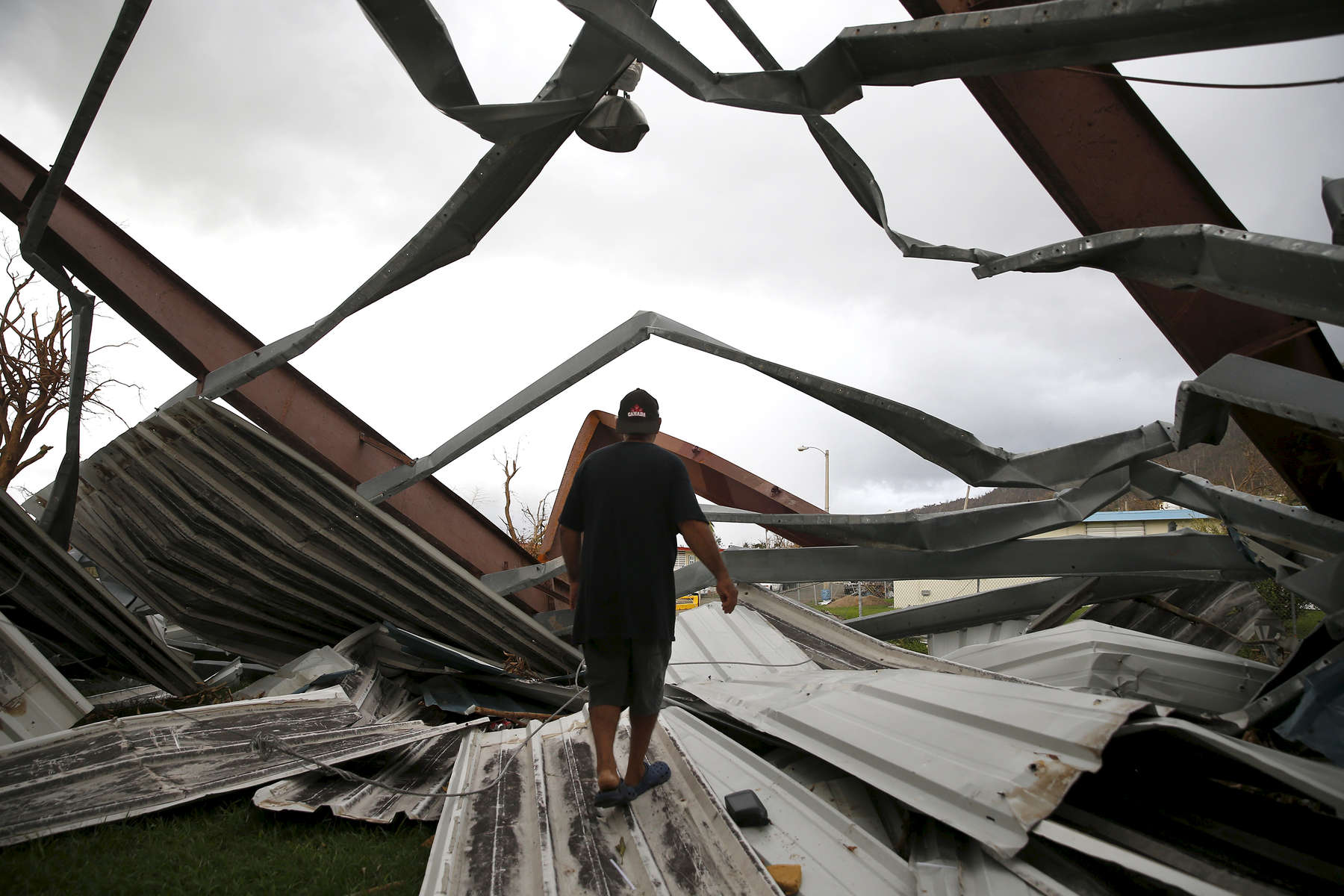 Yabucoa, Puerto Rico -- 9/29/2017 -  In Yabucoa where Hurricane Maria first made landfall, the metal roof and viewing stands from a basketball court across the street were deposited onto Carmen Charriez's home. The family of five, including a nephew, rode out the storm by hiding in a hallway for hours. Nine days later they were still sleeping in plastic lawn furniture in their garage, fearful of their roof collapsing.