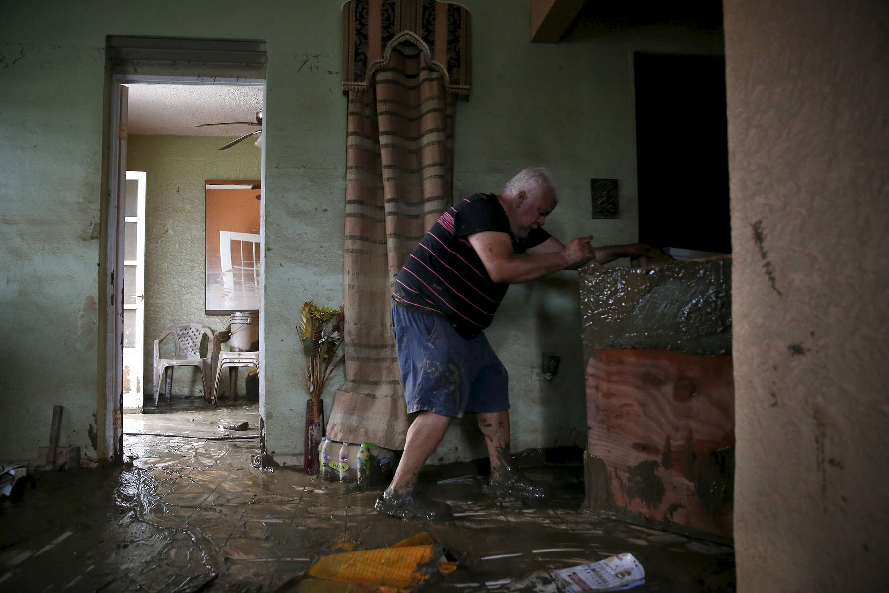 Toa Baja, Puerto Rico -- 9/30/2017 -  In Toa Baja, on the island's northern coast, bulldozers worked to clear mud from the streets as families were digging out, trying to salvage the few belongings that were left. Geraldo Rivera, 51, helps his neighbor move heavy furniture out of his home which was ruined by flood waters.