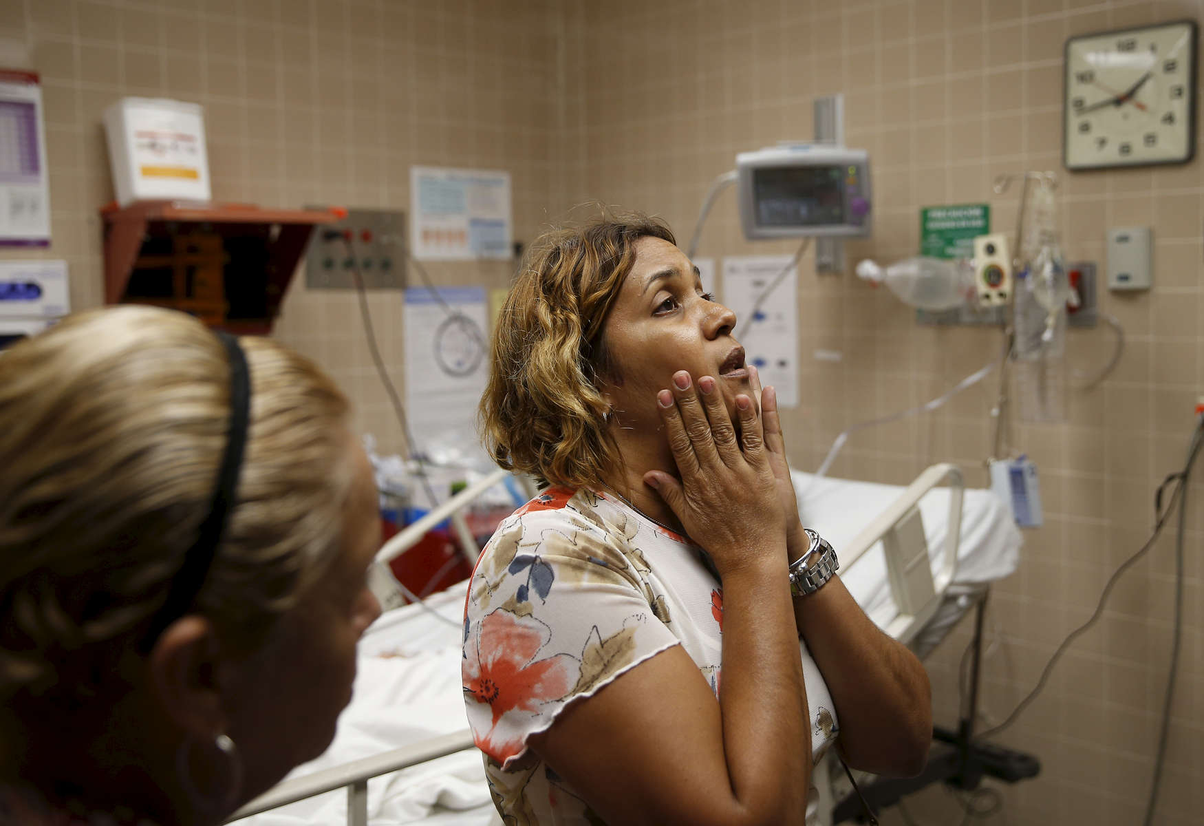 """Caguas, Puerto Rico -- 9/29/2017 -  Myriam Ruiz waits inside the emergency room where her father, Luis Alberto Ruiz, is being treated after attempting to hang himself with his belt. When Myriam found him behind their home, she began to scream. Moments later, two neighbors rushed over and helped pull his limp body down from the roof. There was no way to call an ambulance, so they carried him to their Jeep and sped to the hospital. Her father's medical problems had gotten worse in recent weeks, she explained. He kept worrying about all the trouble he was causing her, and told her he would take care of it. """"There was a lot of stress at the house,"""" she said. """"The hurricane put him over the edge."""""""