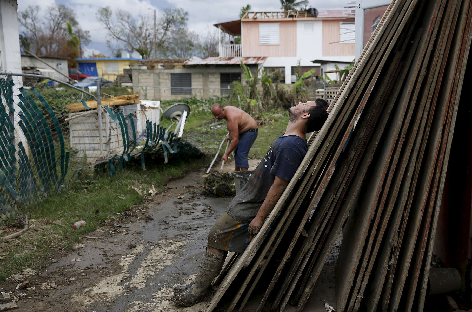 Toa Baja, Puerto Rico -- 9/30/2017 - Ten days after Hurricane Maria hit Puerto Rico, Eric La Luz, 15, and his family were still doing the mentally and physically exhausting work of cleaning out their home. Almost everything in the home was a total loss, but they were eager to move out of the shelter they were living in and get back home. Using a rectangular plastic tub they dragged bin after bin of mud and debris out of their home in Toa Baja.