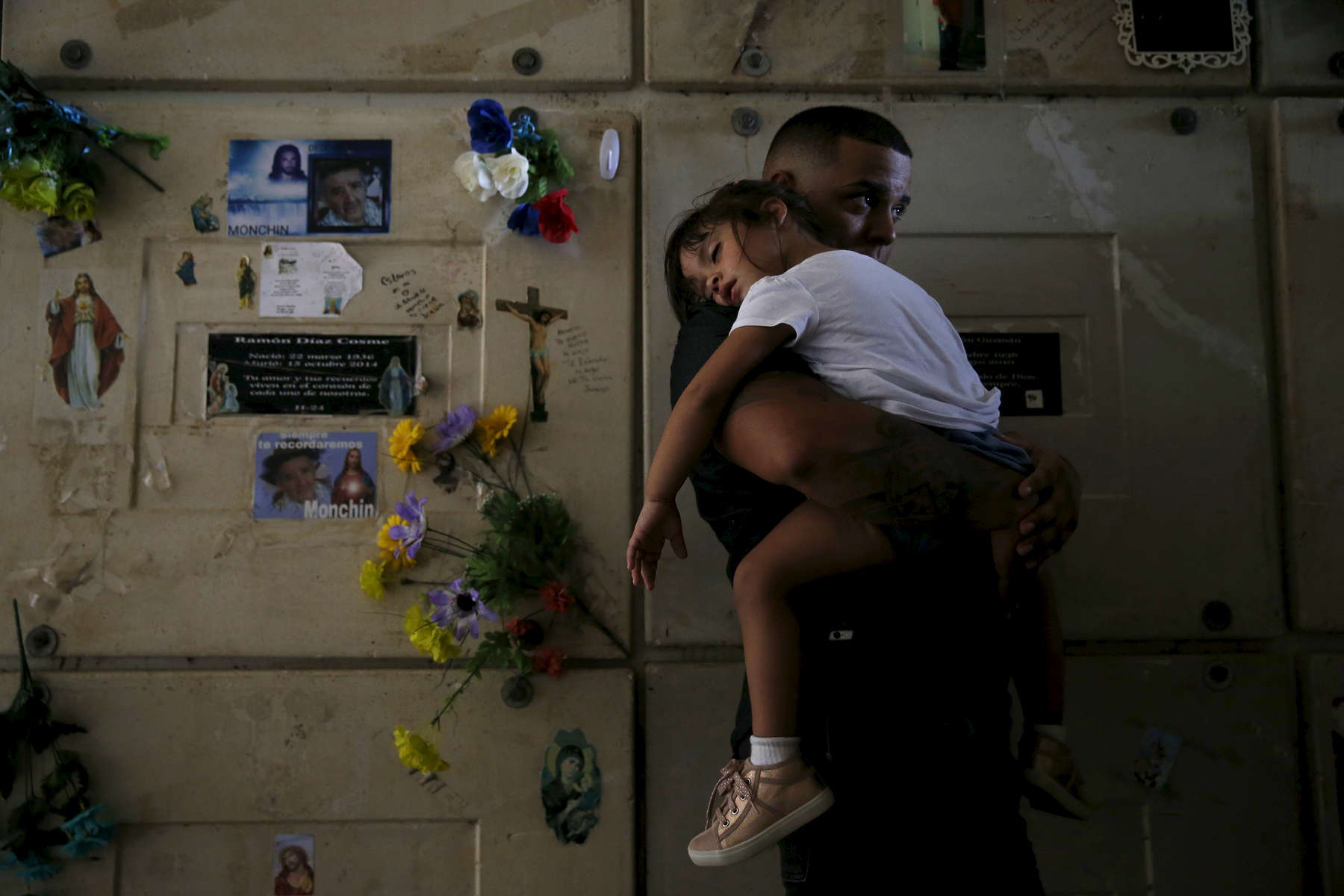 Corozal, Puerto Rico -- 10/02/2017 -  Orlando Gonzalez holds his daughter, Nahielys, inside a mausoleum at their neighbor, Victor Ruiz's funeral. After the storm had knocked power out on the island, Ruiz had been using his car to charge the machine that helped him treat his emphysema. When he started to run low on fuel he went to a nearby gas station. He had waited over 35 hours in line when a nearby explosion sent a plume of smoke up into the air, causing the gas station to be evacuated. Ruiz made it home, but died in his car before he could get out. The death count has not included people like Ruiz, whose death was an indirect result of Hurricane Maria.
