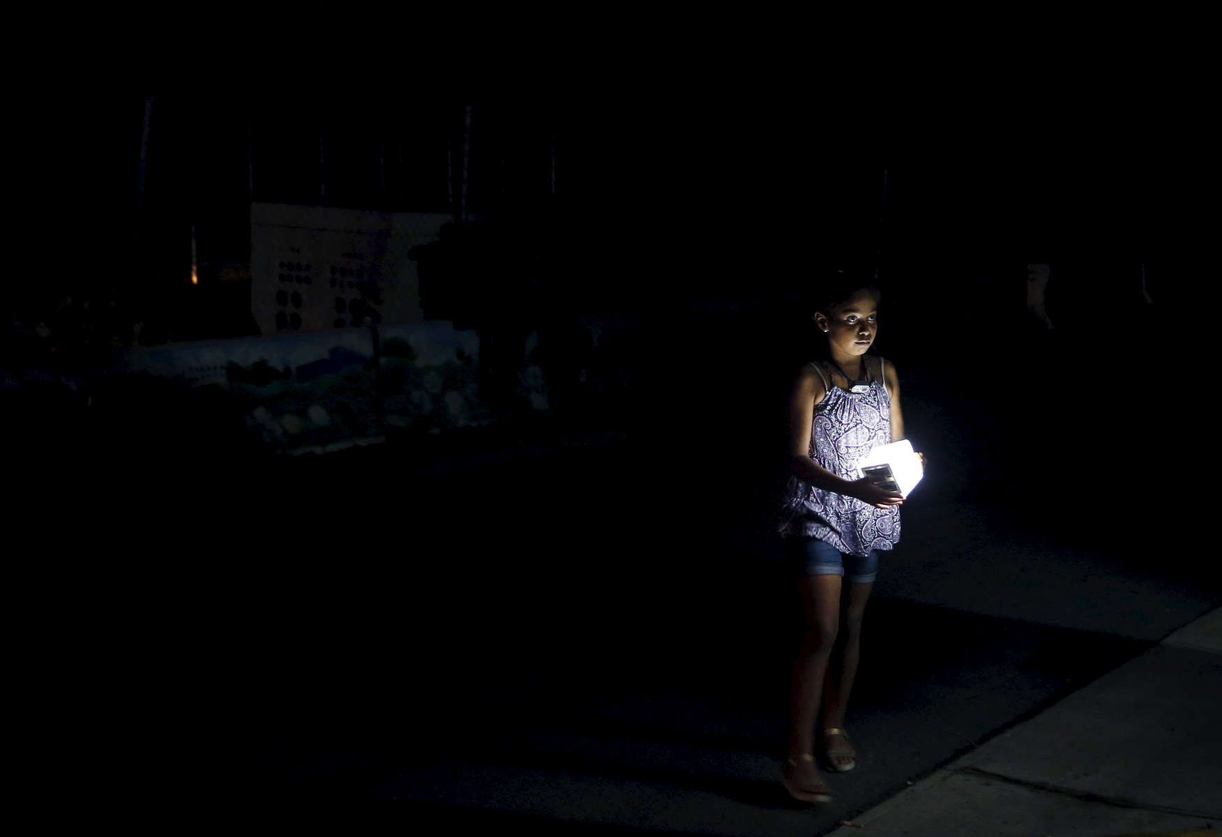 San Juan, Puerto Rico -- 10/01/2017 -   A child, forced into the street with her family to escape the heat inside their public housing apartment, held onto one of the few sources of light in a blacked out San Juan. Nearly four months after Hurricane Maria first made landfall an estimated 40 percent of Puerto Rico is still in the dark.