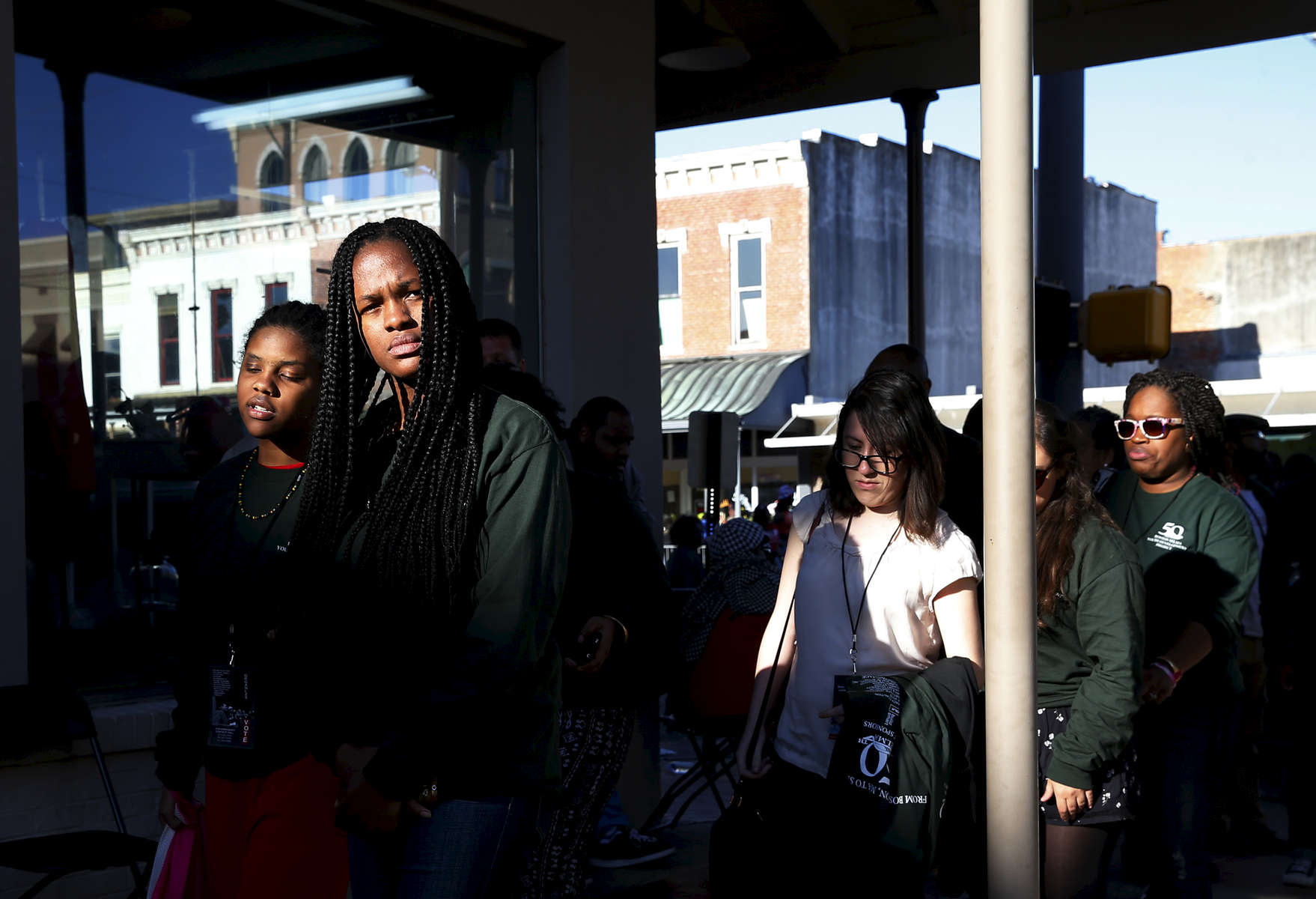 Selma, Alabama -- 3/07/2015-- UMass student Marie Cejour, 24, (2nd from L) links arms with Kaya Van Der Meer, 16, (L) as they walk down a main street in Selma, Alabama with the rest of the members of their group March 7, 2015. Jessica Rinaldi/Globe StaffTopic: Reporter: