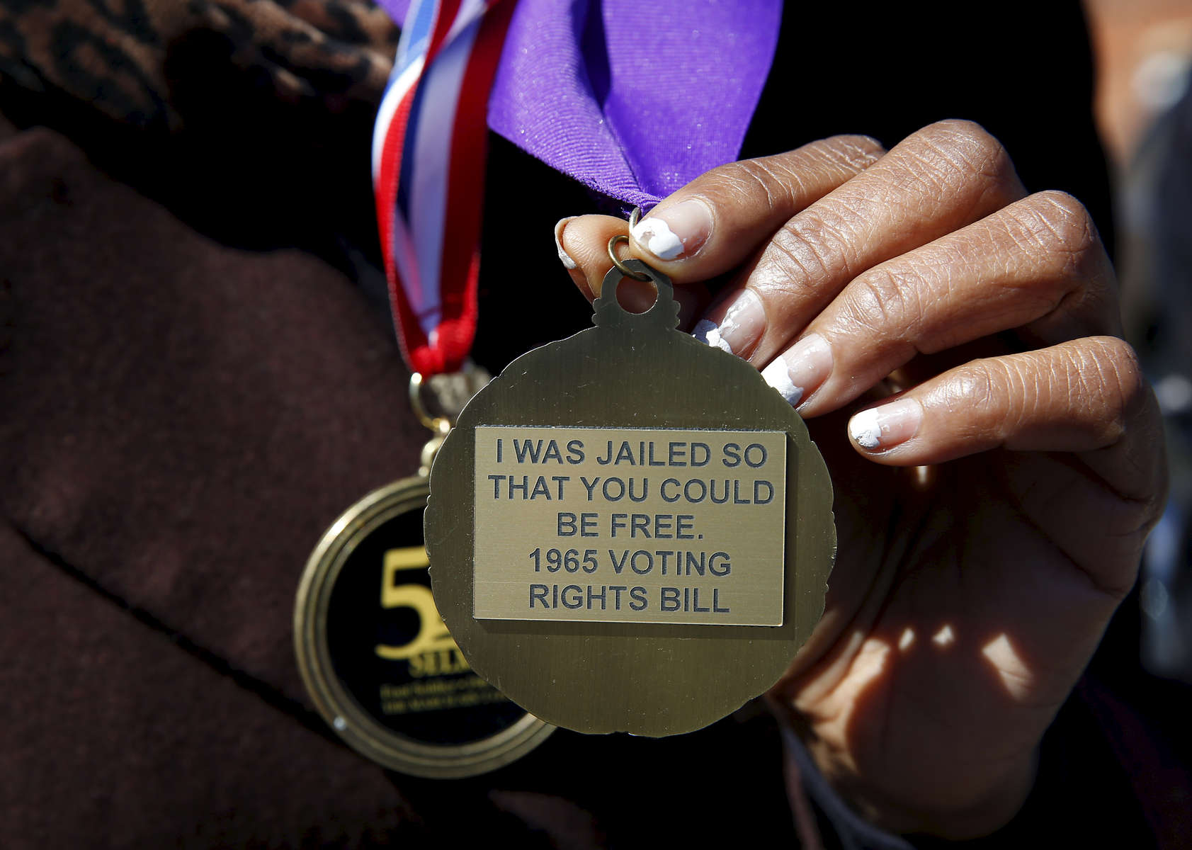 Selma, Alabama -- 3/07/2015-- Linda Hall Gilford of Selma who marched across the Edmund Pettus Bridge at the age of 16 and was beaten as a result shows off the back of a medal in Selma, Alabama March 7, 2015.