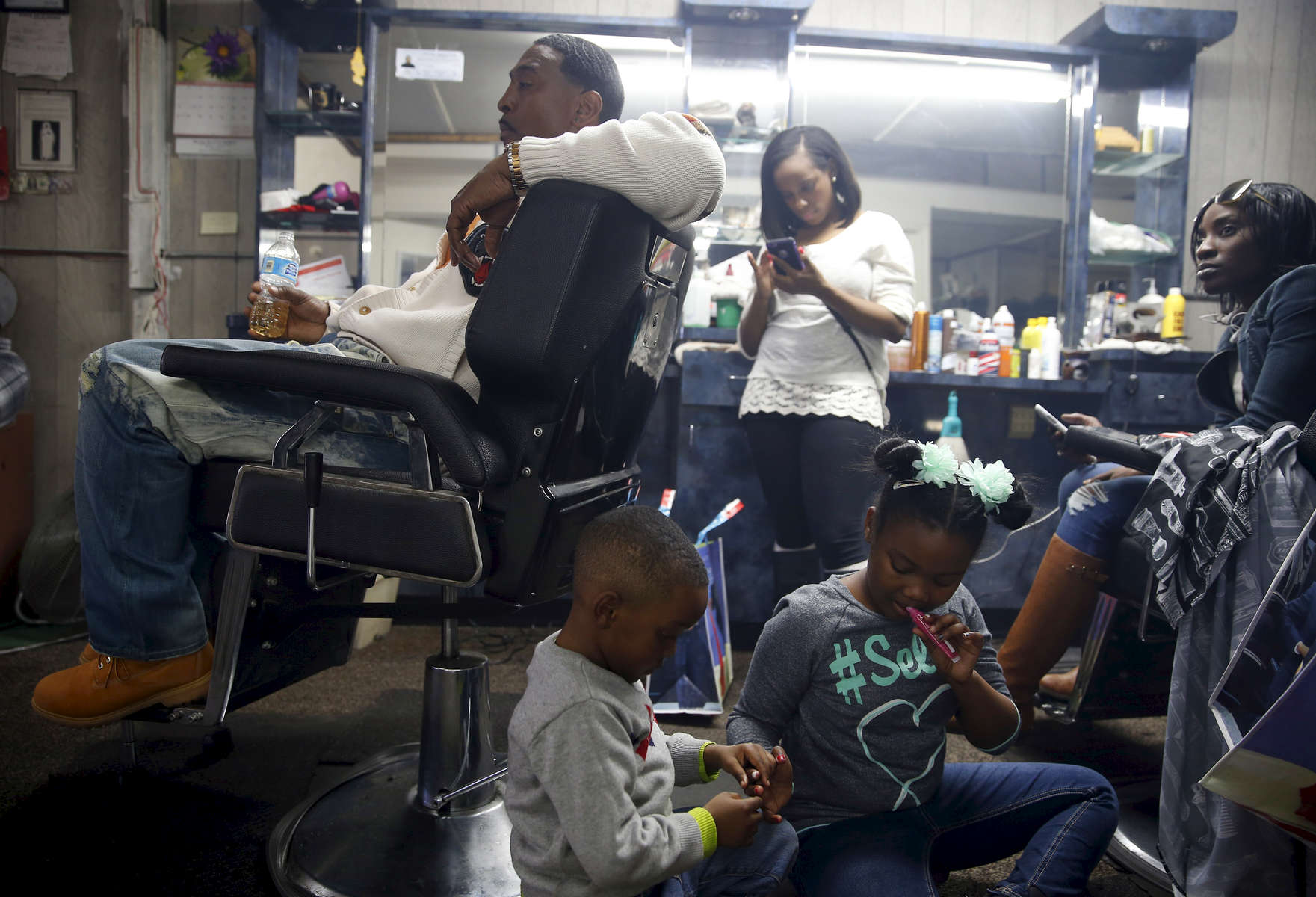 Selma, Alabama -- 3/07/2015-- Children play as people watch President Obama deliver a speech on a television set inside at Ray\'s Bar-B-Que Sandwich Shop which also doubles as a barber shop in Selma, Alabama March 7, 2015. Jessica Rinaldi/Globe StaffTopic: Reporter: