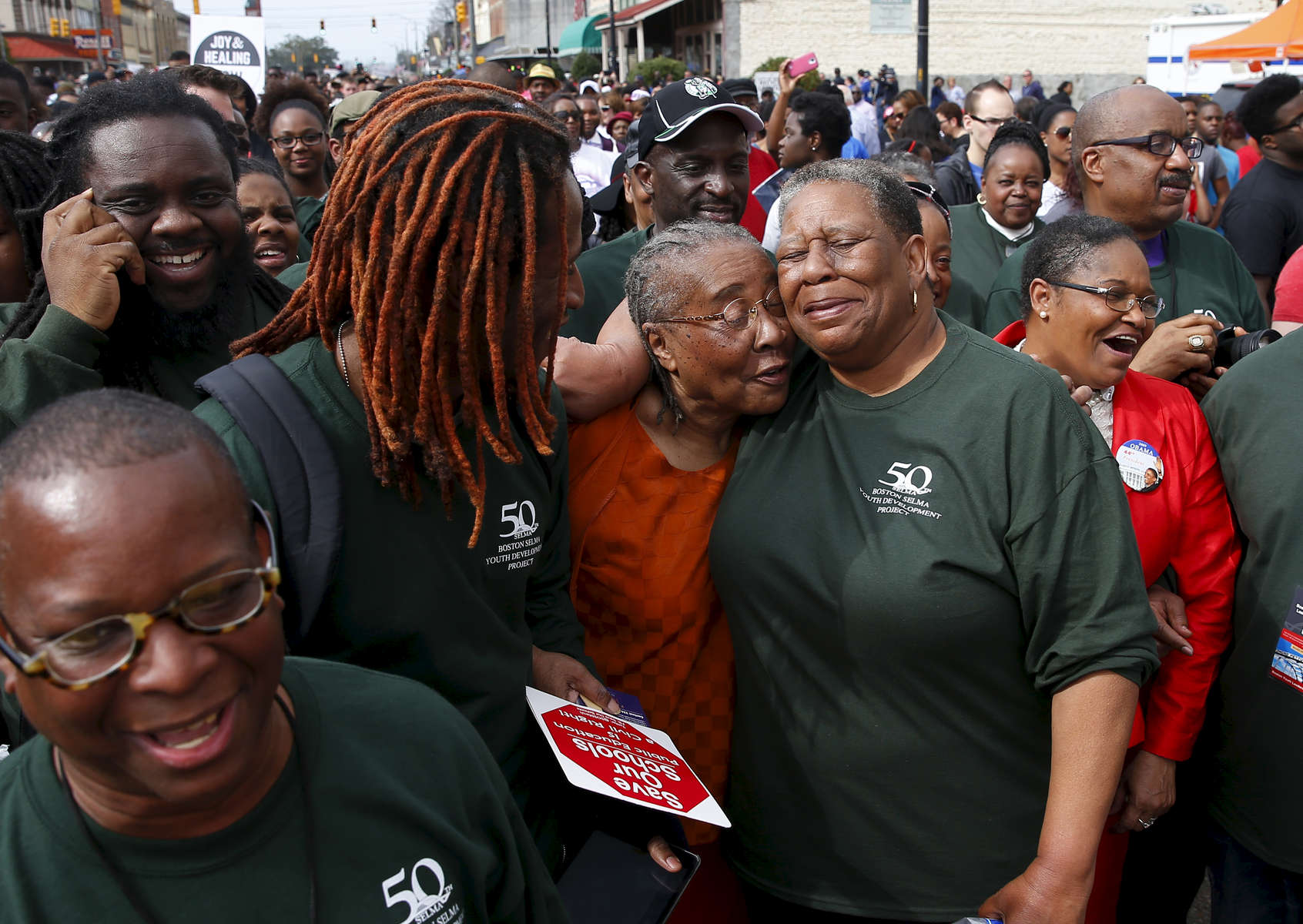 Selma, Alabama -- 3/08/2015-- (L-R) Kevin Peterson of the New Democracy Coalition, UMass student Vonds Dubuisson, 27, smile as Gloria Patterson, of Detroit hugs Joanne Bland, of Selma who was one of the original marchers  who marched with Dr. Martin Luther King, Jr. over the Edmund Pettus Bridge on Bloody Sunday, as her older sister, Lynda Blackman Lowery laughs as Patterson appears on a documentary playing out over the crowd of people ready to retrace the steps of those who marched with Dr. Martin Luther King, Jr. over the Edmund Pettus Bridge 50 years ago in Selma, Alabama March 8, 2015. Jessica Rinaldi/Globe StaffTopic: 09selmaReporter: