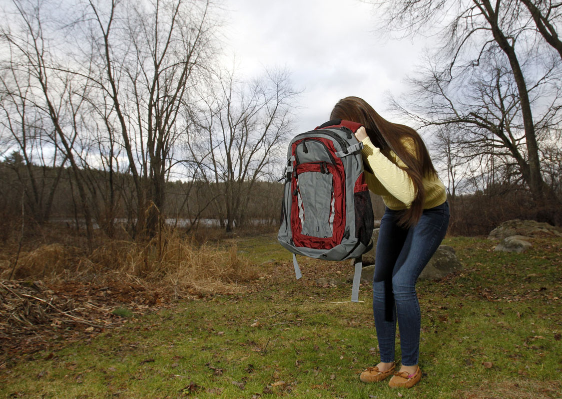 Amanda Curran, 18, daughter of Bullet Blocker inventor Joe Curran, demonstrates how to use a child's bulletproof backpack in the event of a shooting outside of Curran's home in Billerica, Massachusetts December 19, 2012. The child's bulletproof backpacks range in cost from $250 to $600 depending on the size of the backpack. According to Bullet Blocker Vice President of Business Operations Elmar Uy their products stop 99.9% of bullets from all handguns. REUTERS/Jessica Rinaldi