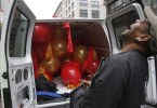 A man transporting balloons laughs as police officers watch him pop the remaining balloons in order to make the used arrangement fit inside his delivery van in the Chinatown section of Boston, Massachusetts June 4, 2012.