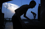 People are silhouetted as they play on a rope swing over the James River in Richmond, Virginia June 21, 2012.
