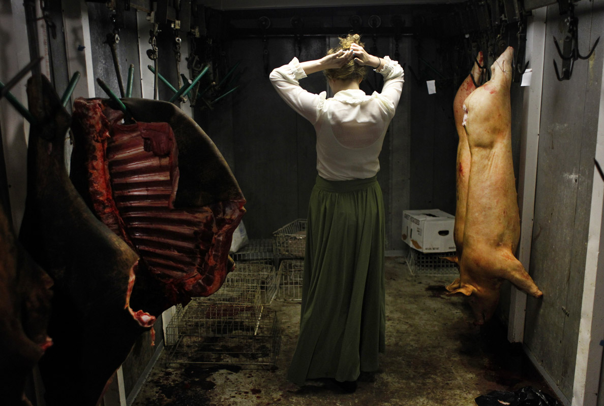 Artist Sascha Hughes-Caley fixes her hair inside a meat locker in Providence Forge, Virginia.