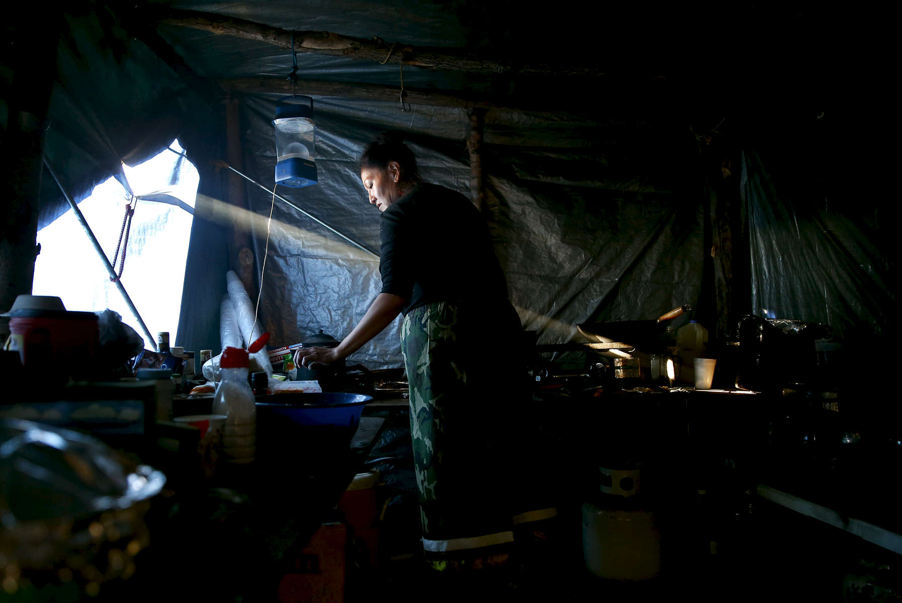 Lelani Running Bear, of the Standing Rock Reservation, prepares a meal for members of High Star camp. She moved here in August from her home on the Standing Rock Indian Reservation to protest the Dakota Access Pipeline. Since then, her makeshift kitchen has become a kind of sanctuary for both her and others — a place to escape the anxiety, uncertainty, and fear that have come to define life here.