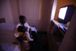 Annette Wilson (R) watches television with her daughter, Dorche Woods, 4, (L) in the motel room where the family is living in Grand Prairie, Texas June 30, 2009.