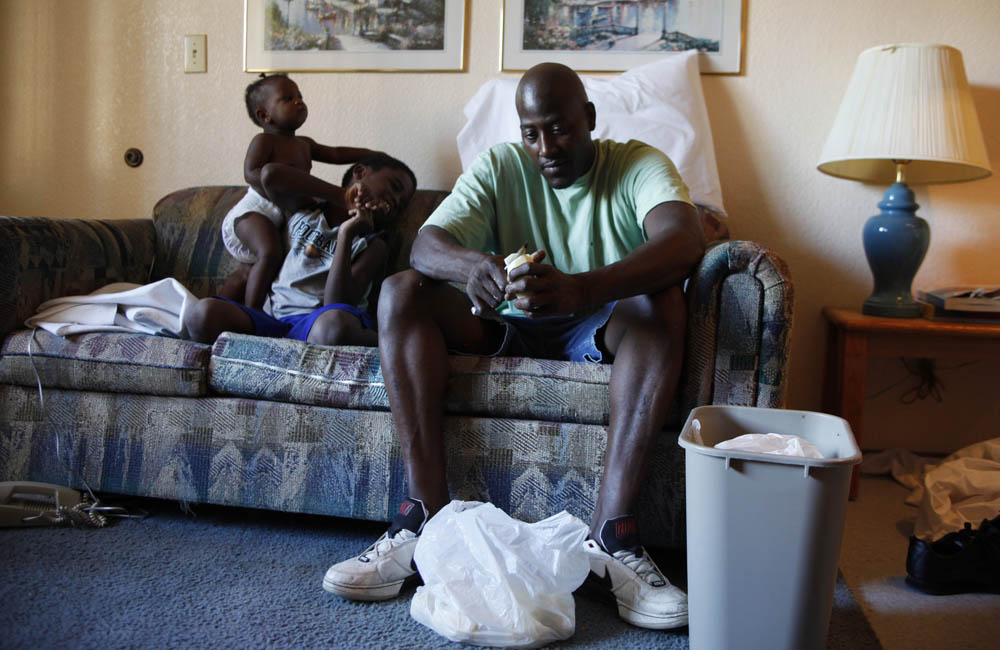 Frederick Wilson, (R), peels potatoes as his nephew, Javonte Miles, 10, (C) and granddaughter Keziah Bradley, 11 months, (L), play on the couch in the motel room where the family is living in Grand Prairie, Texas July 1, 2009. The Wilson family moved to Texas after losing their jobs and their home in Minnesota. They ended up in a homeless shelter and through assistance with the National Urban League were able to find jobs, the Urban League has been paying for temporary housing in a motel as they work to get back on their feet.