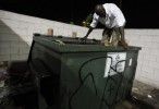 Frederick Wilson lowers himself into a dumpster to compact the trash he threw away at a gas station where he works nightly, taking out the trash and mopping the floors in exchange for ten dollars pay, in Grand Prairie, Texas June 30, 2009.