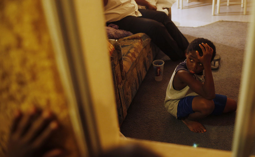 Javonte Miles, 10, is seen through the window of the motel room where his family lives in Grand Prairie, Texas July 1, 2009.