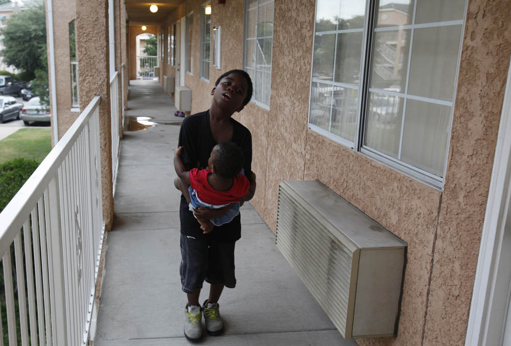 Javonte Miles, 10,  caries his 11-month-old cousin, Keziah Bradley, down the hallway leading to the motel room where he and his family live in Grand Prairie, Texas July 2, 2009.