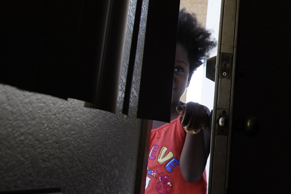 Dorche Woods, 4, peeks her head into the motel room where she and her family are living in Grand Prairie, Texas July 2, 2009.