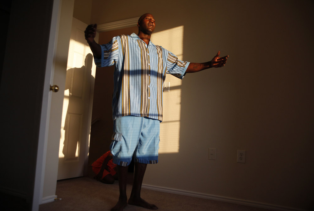 Frederick Wilson raises his hands to the window as he thanks God for his new home as the family inspects their new low income apartment in Grand Prairie, Texas July 2, 2009. The Wilson family moved to Texas after losing their jobs and their home in Minnesota. They ended up in a homeless shelter and through assistance with the National Urban League were able to find jobs, the Urban League is paying the rent on their new apartment as they work to get back on their feet.