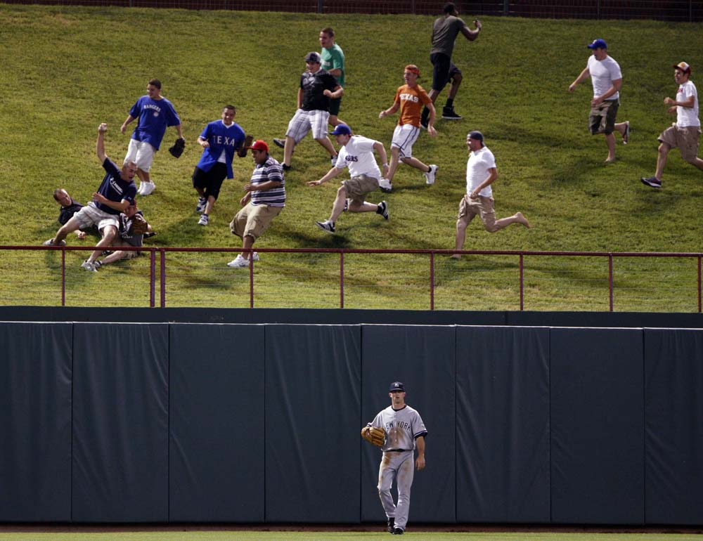New York Yankees right fielder Nick Swisher walks away as Texas Rangers fans grab the home run ball hit by Rangers' Chris Davis during the fourth inning of American League MLB baseball action in Arlington, Texas May 26, 2009.