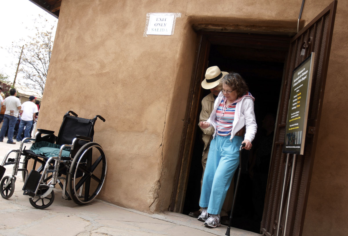 Mel Ortiz helps his wife, Catalina, out of the door after the two made their pilgrimage to El Santuario de Chimayo in Chimayo, New Mexico April 23, 2011. Thousands of people walk to the little chapel over Easter weekend, where they believe the dirt inside holds the power to heal, some from as far away as Mexico and Colorado.