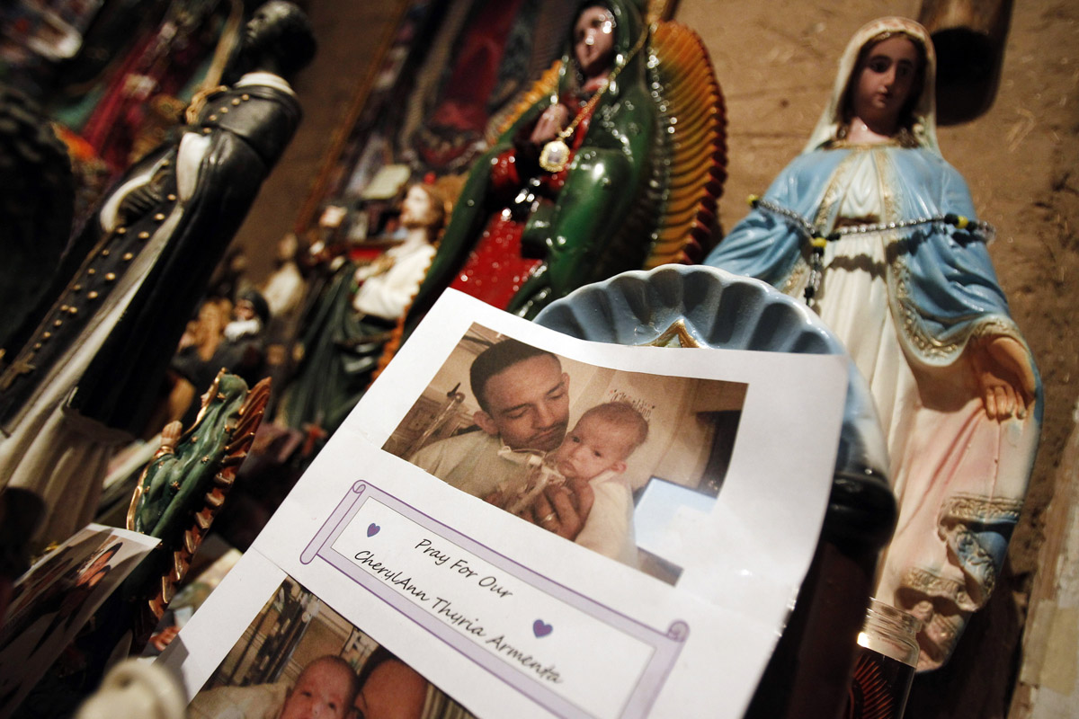 A photo of a man and baby which reads, {quote}Pray For Our CherylAnn Thuria Armenta{quote} has been left beside a statuette of the Virgin Mary at El Santuario de Chimayo in Chimayo, New Mexico April 23, 2011. Thousands of people walk to the little chapel over Easter weekend, where they believe the dirt inside holds the power to heal, some from as far away as Mexico and Colorado.
